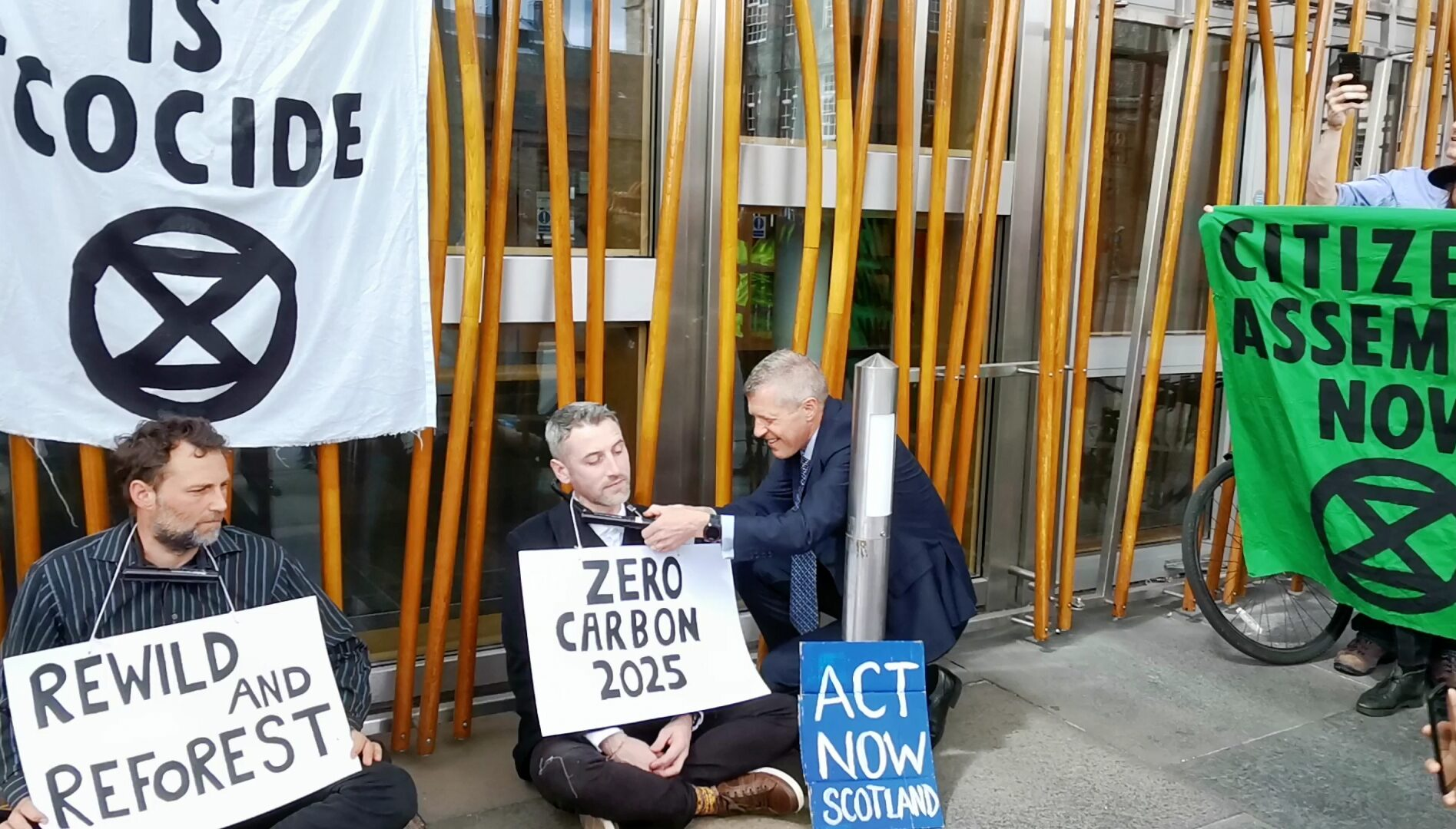 Scottish Liberal Democrat leader Willie Rennie unlocking a climate change activist outside the Scottish Parliament in Edinburgh (Tom Eden/PA)