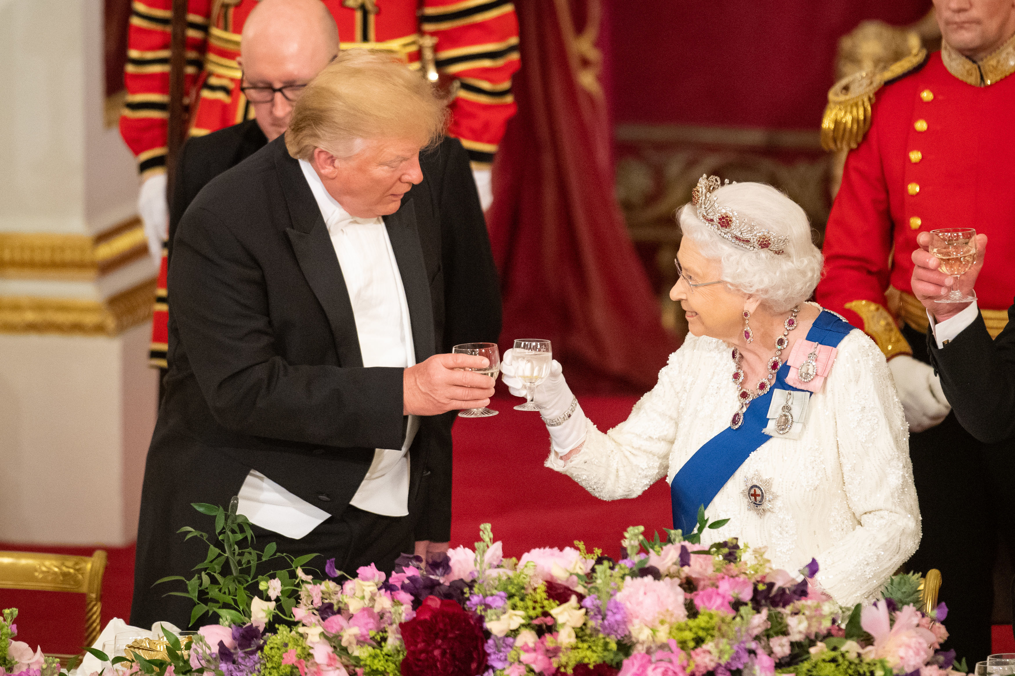 Mr Trump touches glasses with the Queen