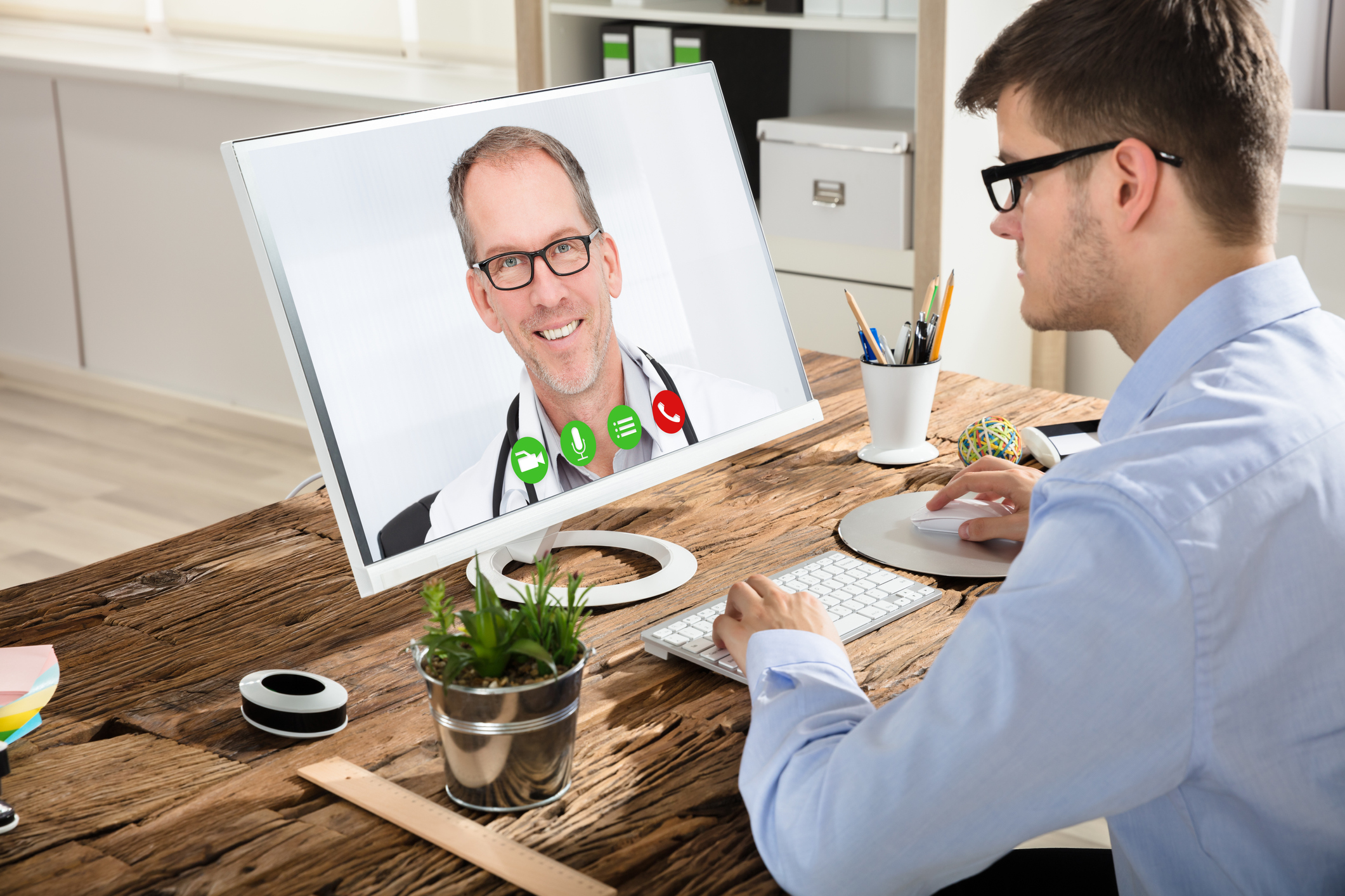 Young Businessman Video Conferencing With Smiling Male Doctor On Computer In Office