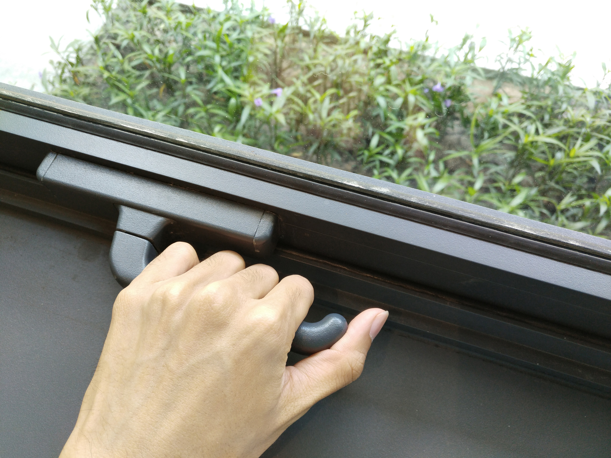 Hand opening, locking window securely, to protect from unwanted things like insects, bugs, fly, birds, pollution (noise, gas, water), unknown person. (Lock and open Concept, cannot come in, be alone)
