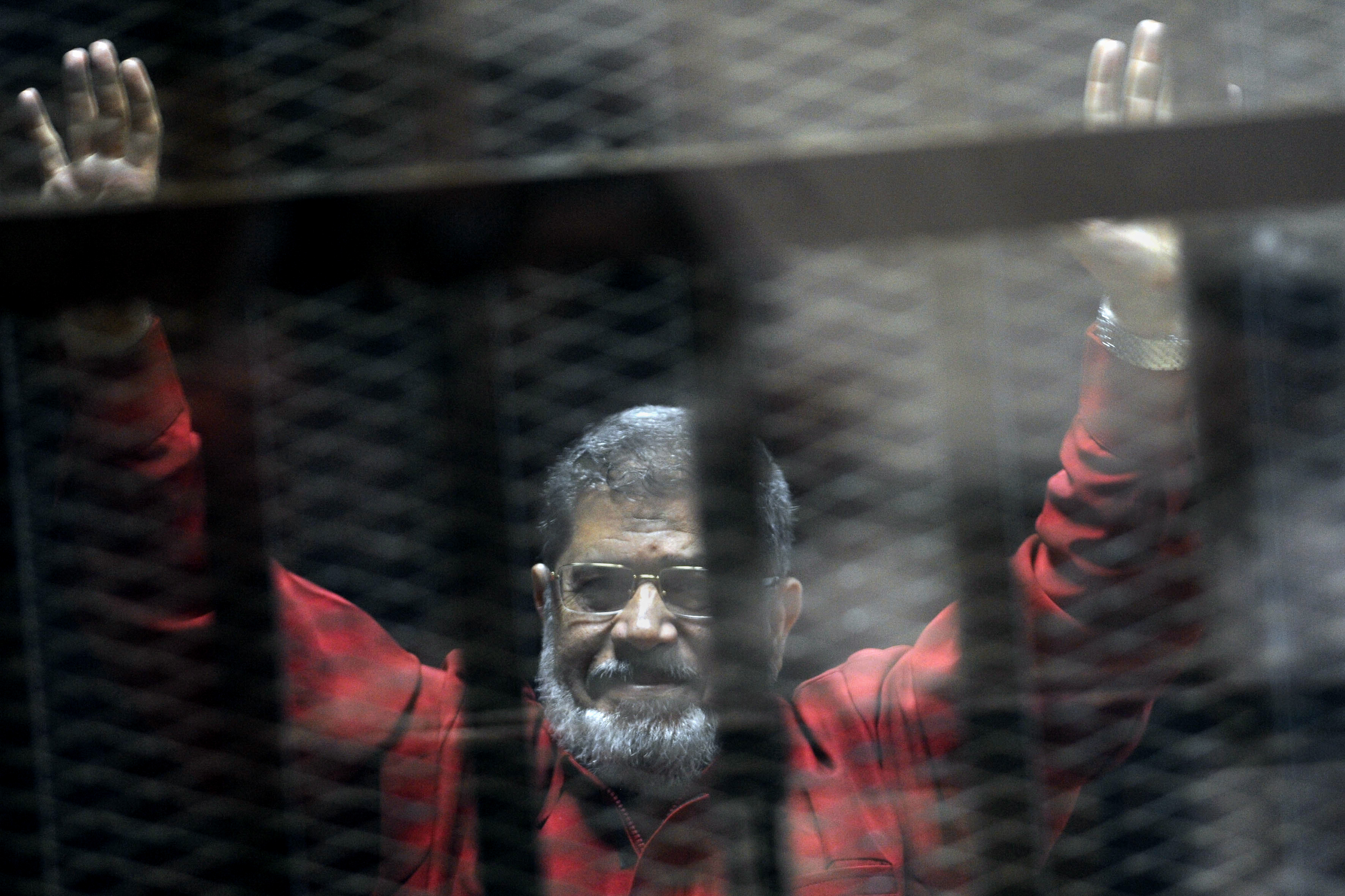 Former Egyptian president Mohammed Morsi wearing a red jumpsuit in a makeshift courtroom in 2015