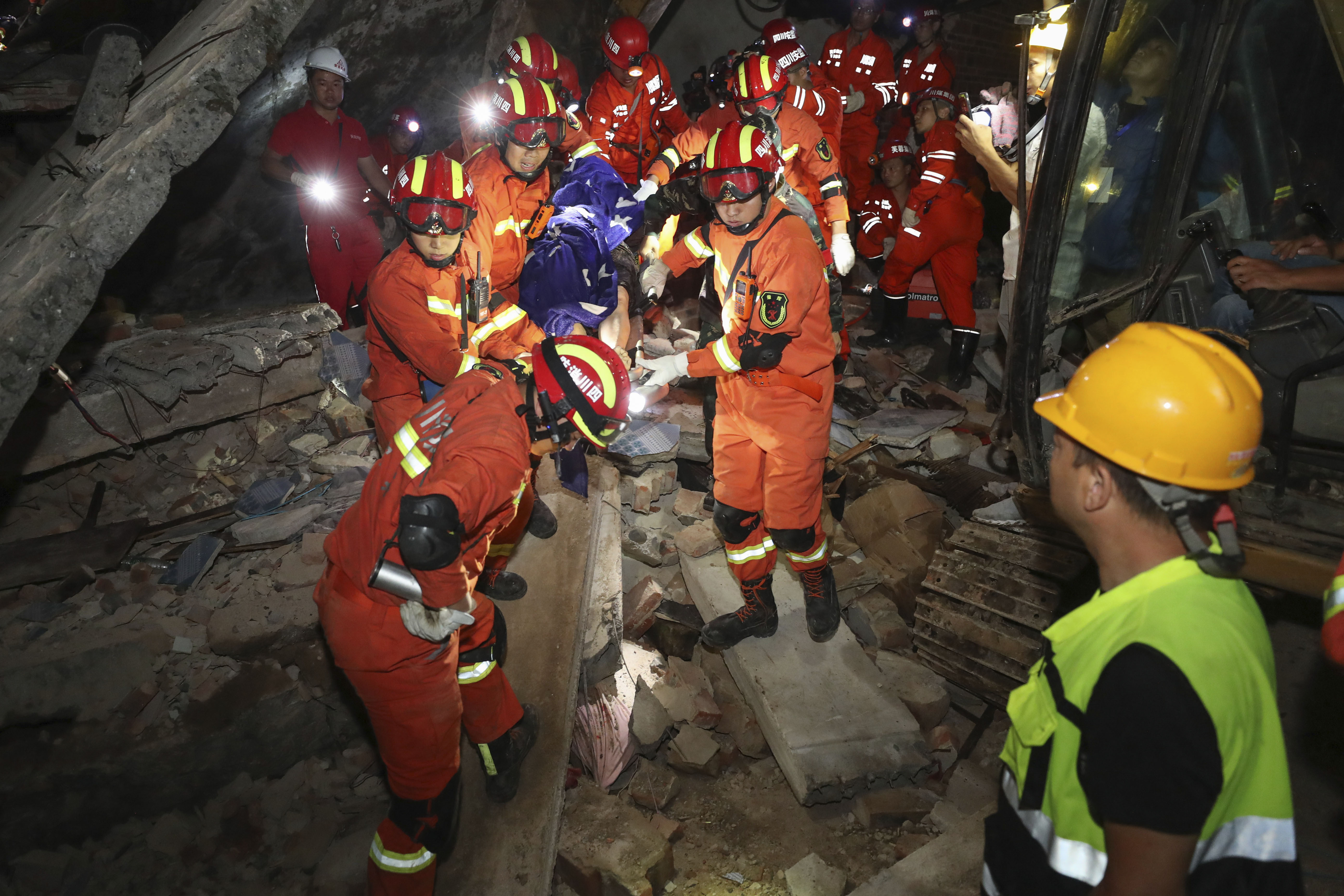 Rescue workers carry out a person from the collapsed building