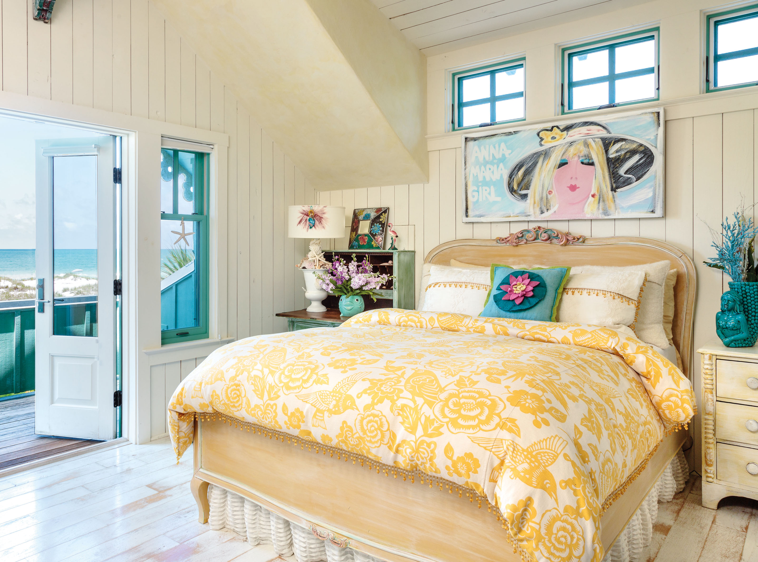 White painted floorboards and pale yellow walls and ceiling create a sunny, shore side room, while a fish shaped vase and a duvet cover decorated with hummingbirds and flowers are the perfect finishing touches in Kandice Ridley's home ( Mark Lohman/Global Bohemian/Cico Books/PA)