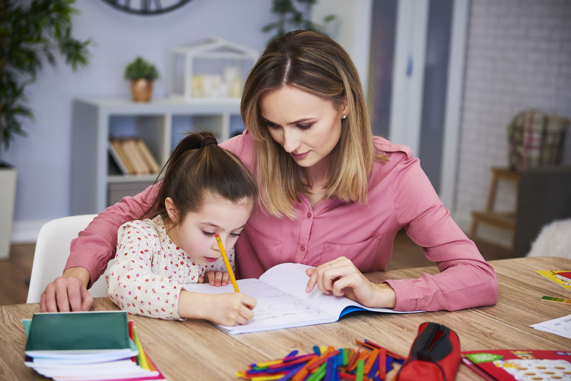 Affectionate mum helping her daughter with homework