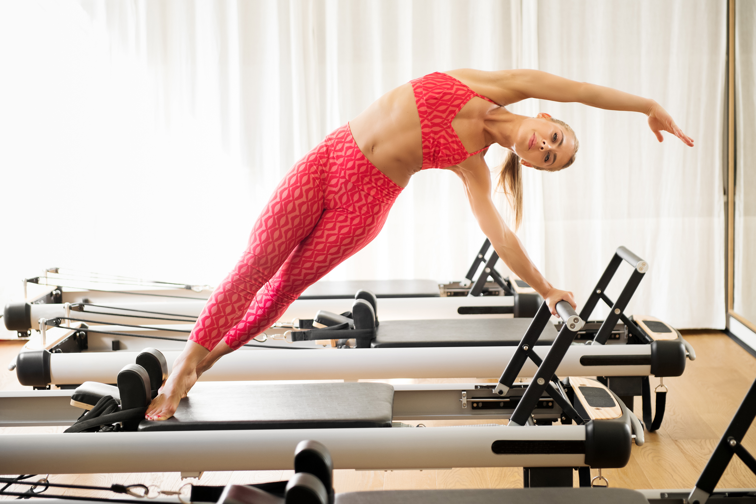 Generic stock image of a woman doing a standing mermaid stretch on a pilates reformer bed at gym. See PA Feature WELLBEING Reformer. Picture credit should read: iStock/PA. WARNING: This picture must only be used to accompany PA Feature WELLBEING Reformer.