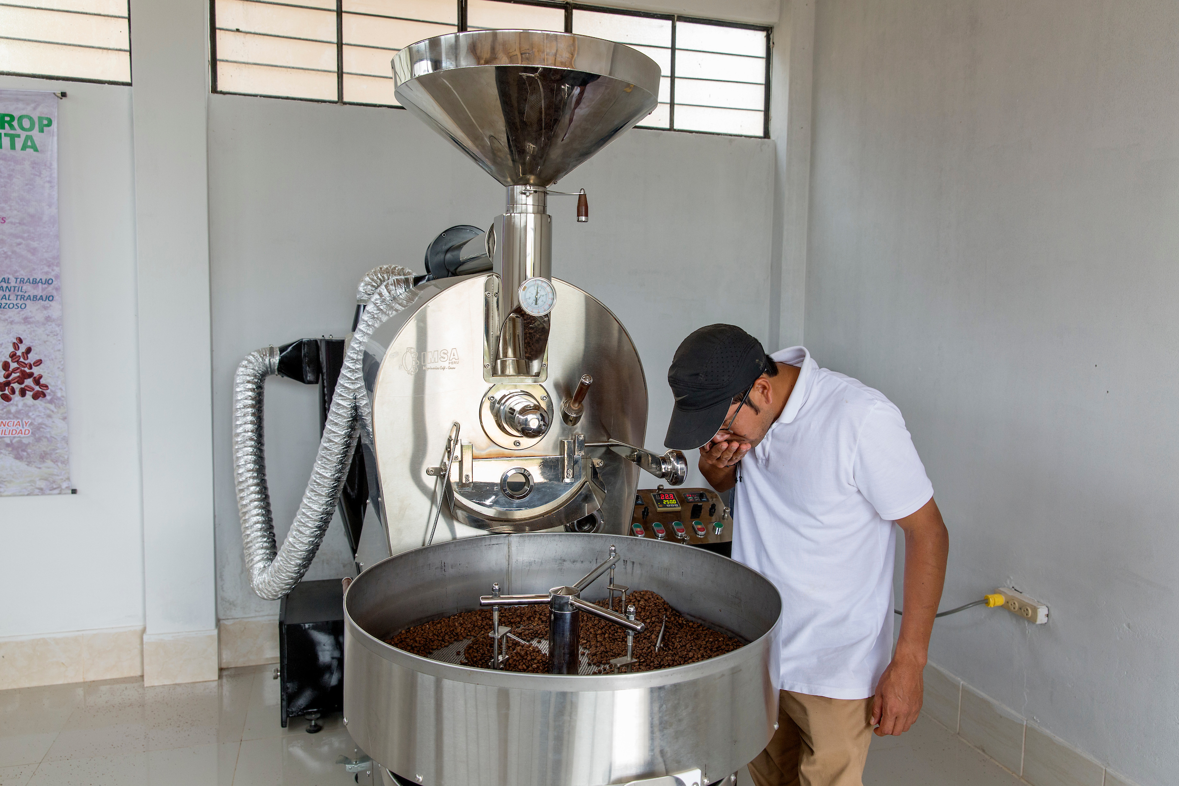 Hugo Javier Guerrero smells freshly-roasted beans at the family farm in Piura