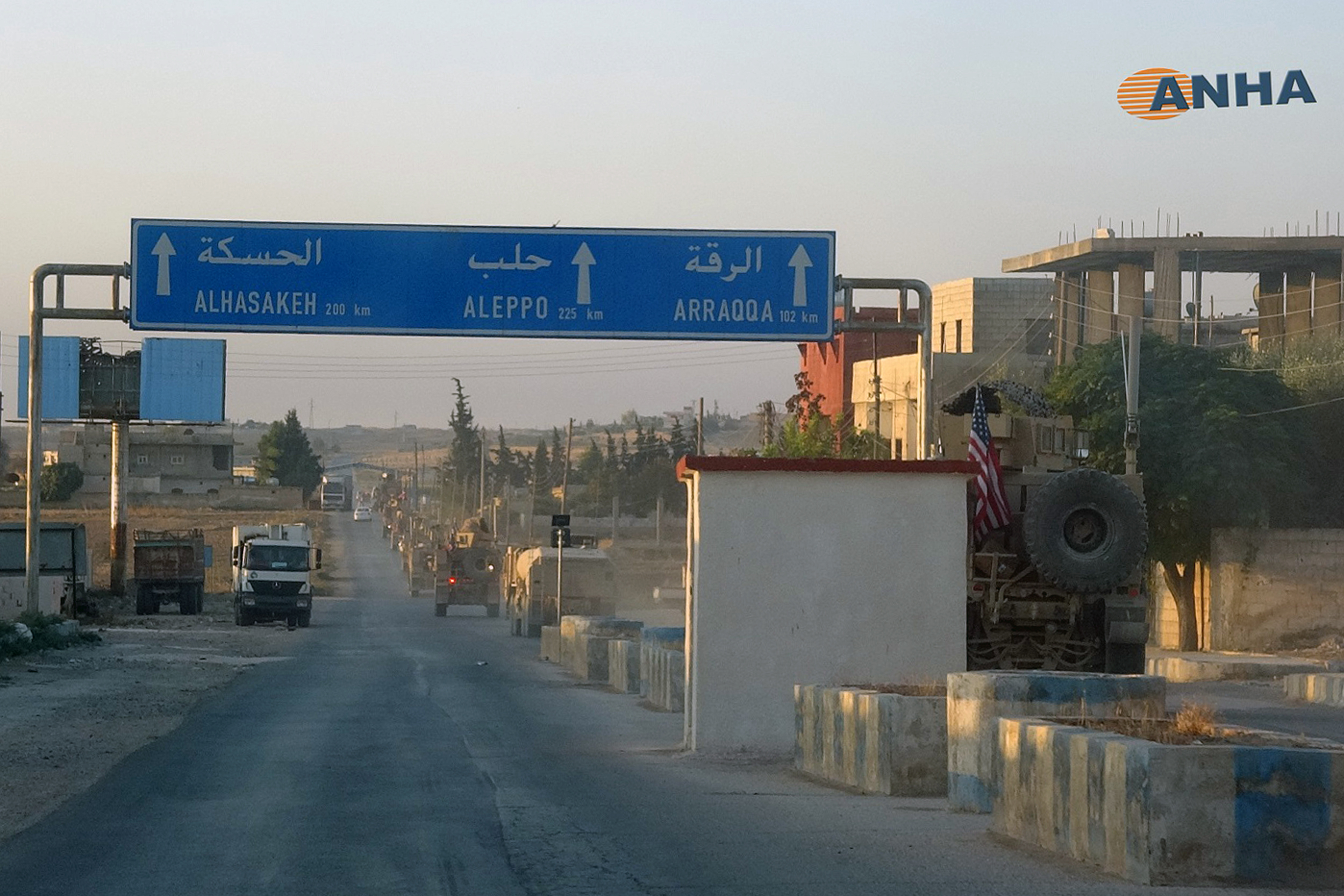 A line of US military vehicles travel down a main road in north east Syria