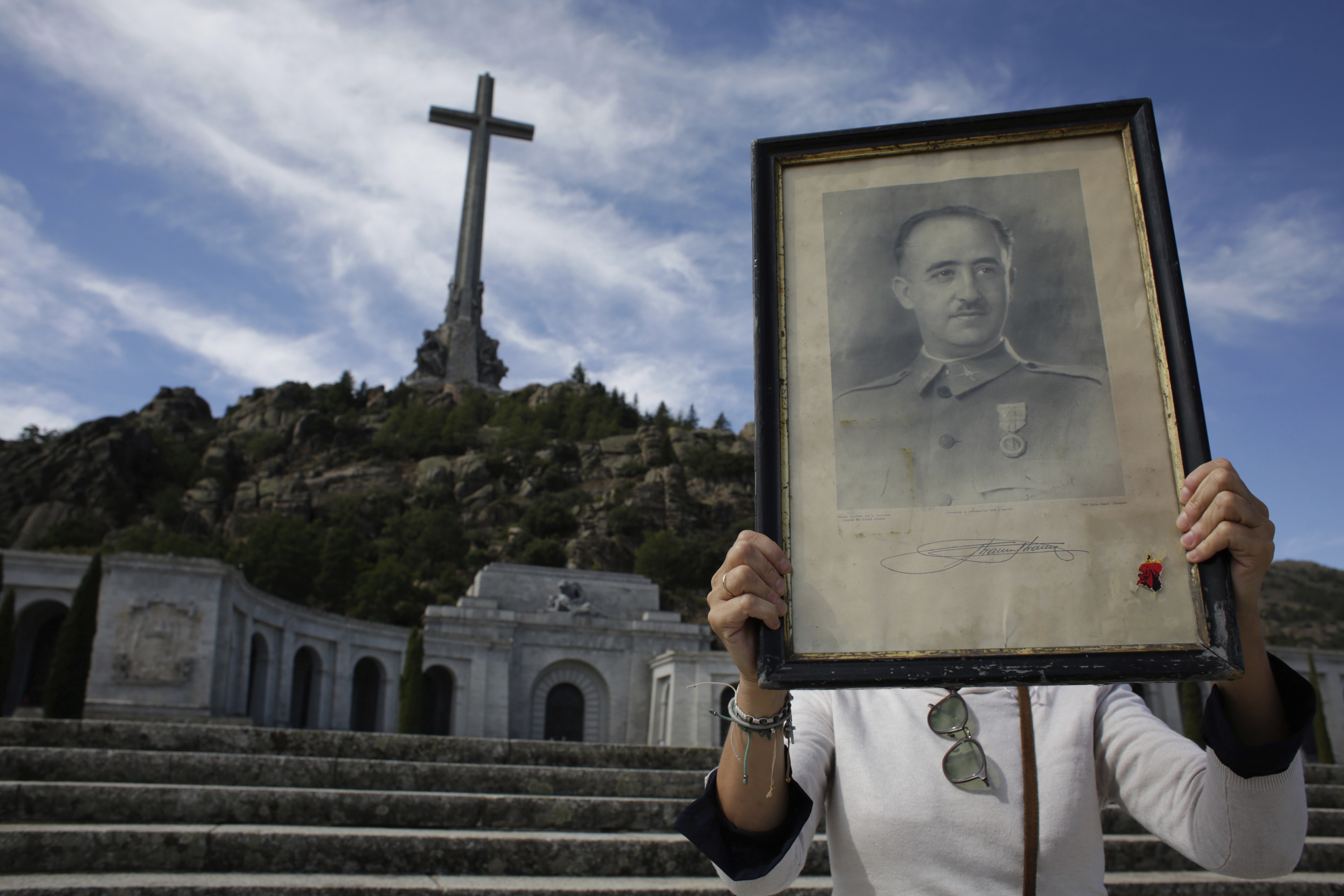 A visitor holds a portrait of former Spanish dictator Francisco Franco at the Valley of the Fallen mausoleum