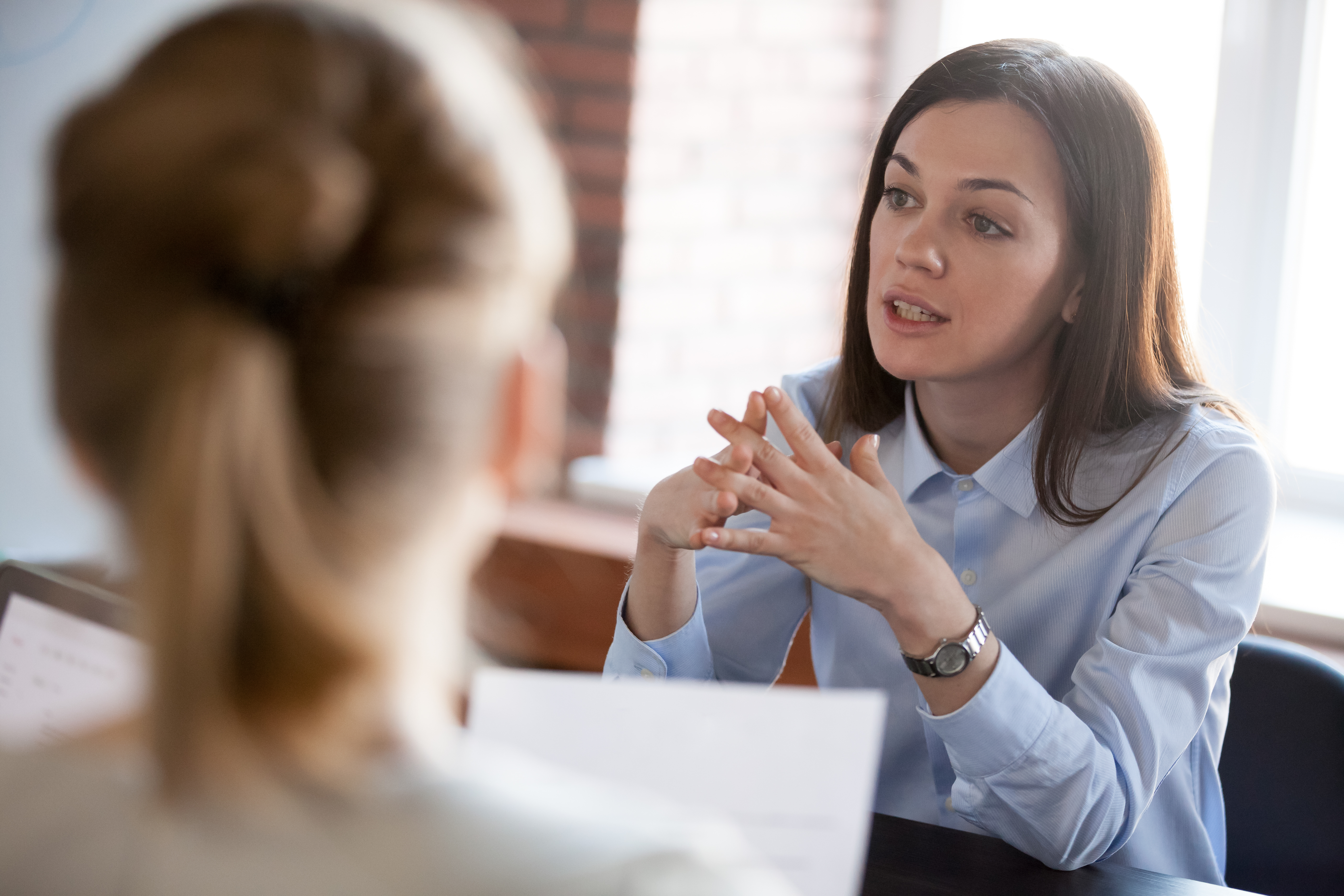 Confident focused businesswoman speaking to people at business negotiations