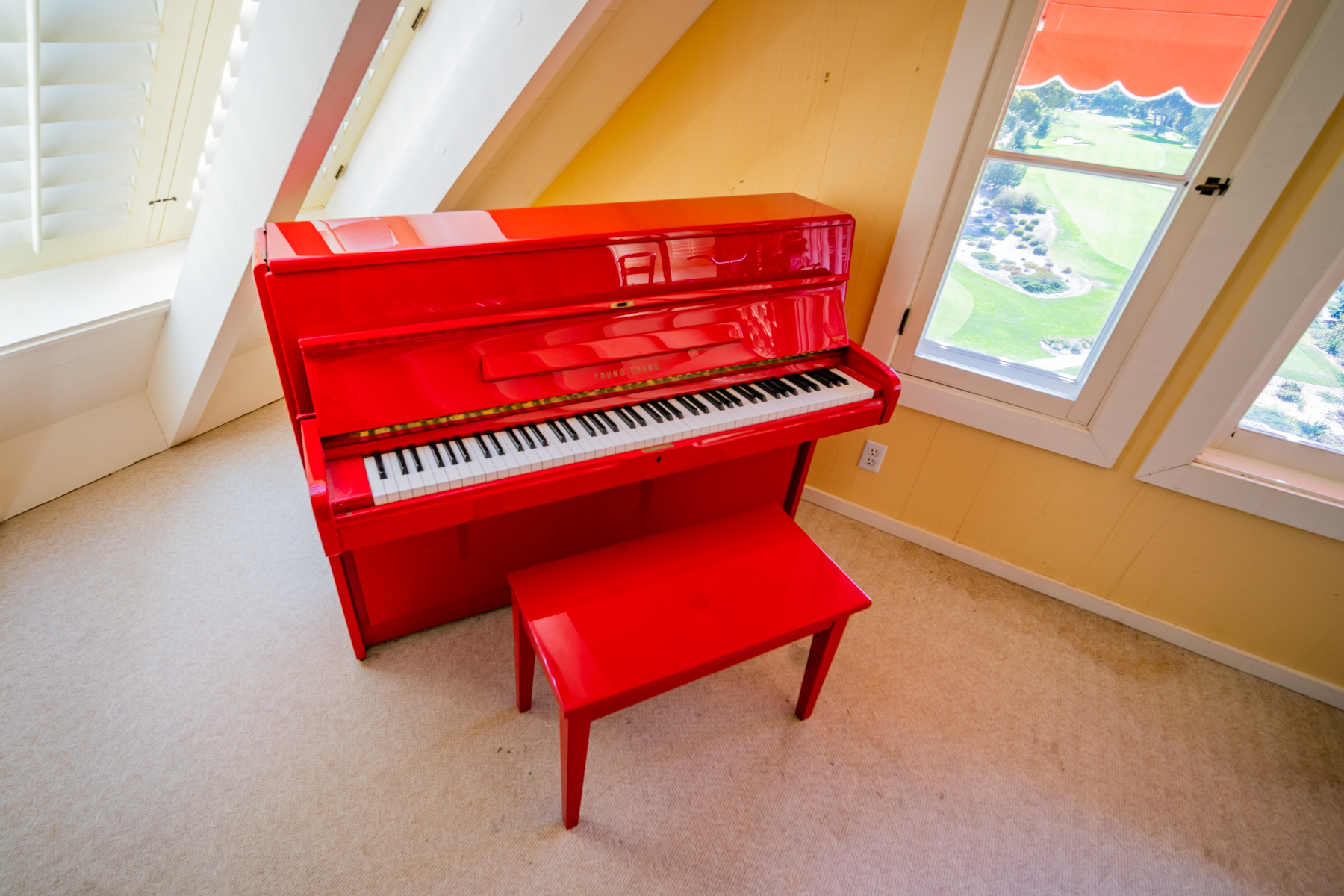 Day's red lacquer Young Chang upright piano