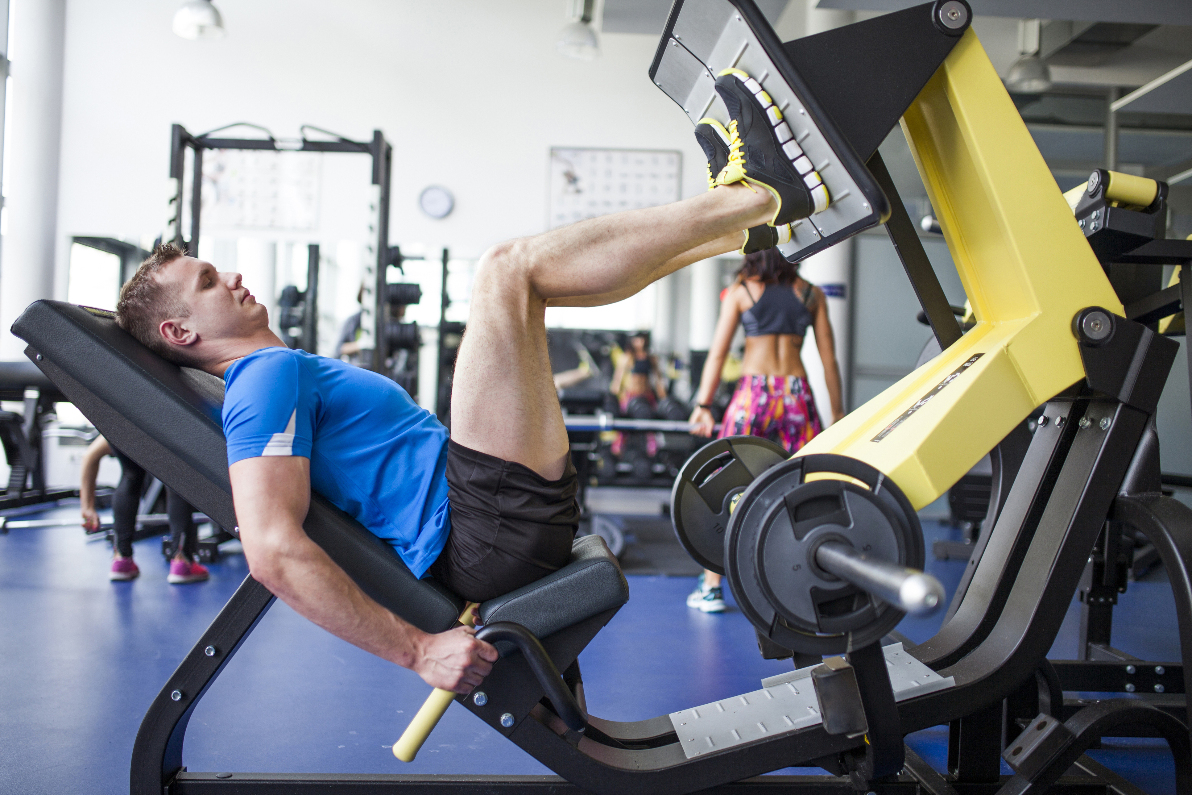 Young people in gym - leg press workout