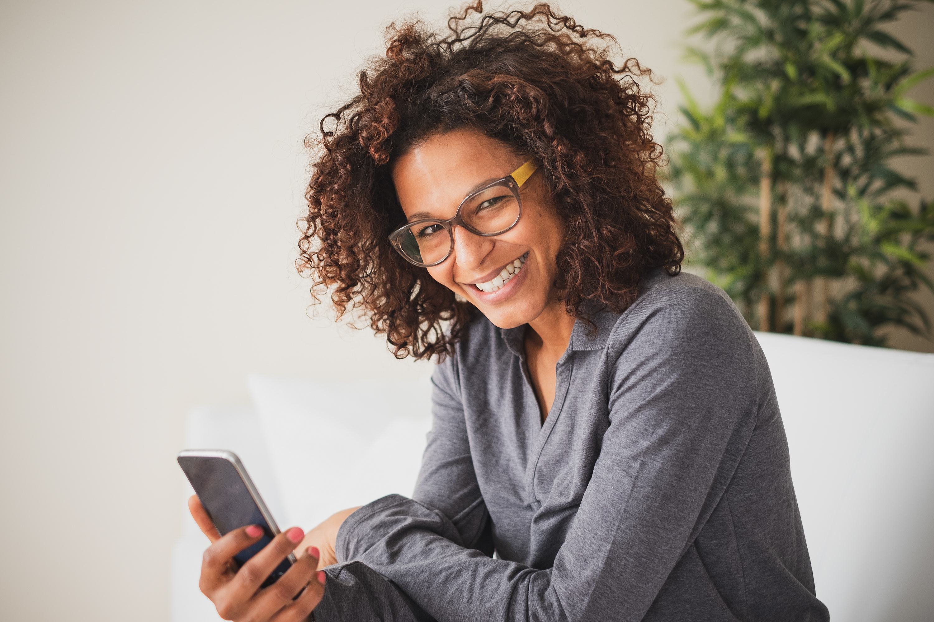Social networks. Young black woman messaging on smartphone at home
