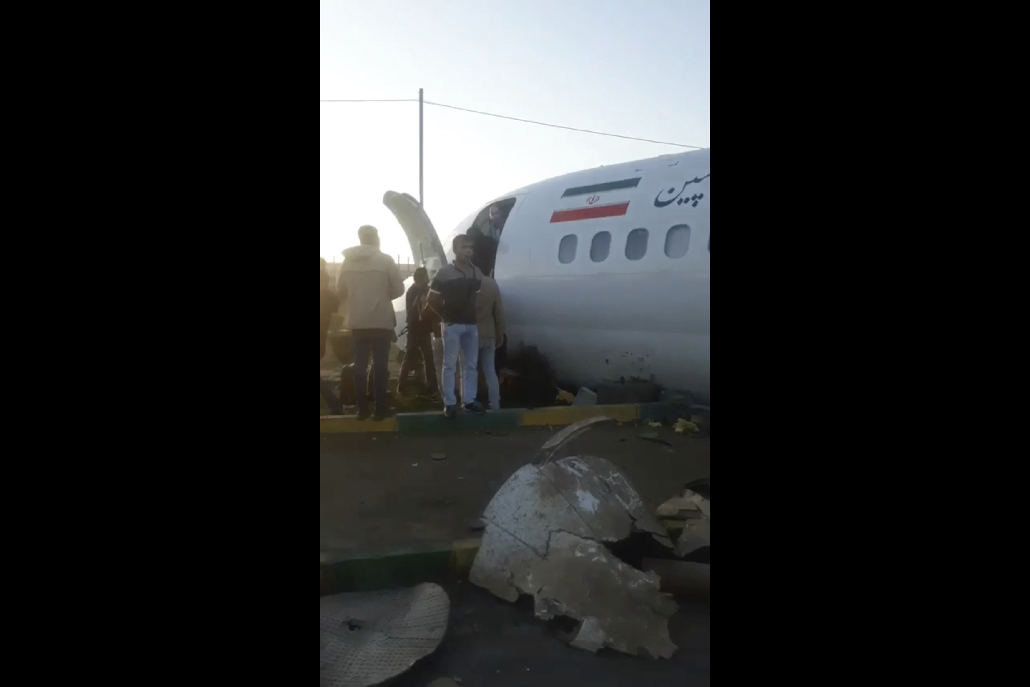 Passengers walk off a crashed plane in Mahshahr, Iran