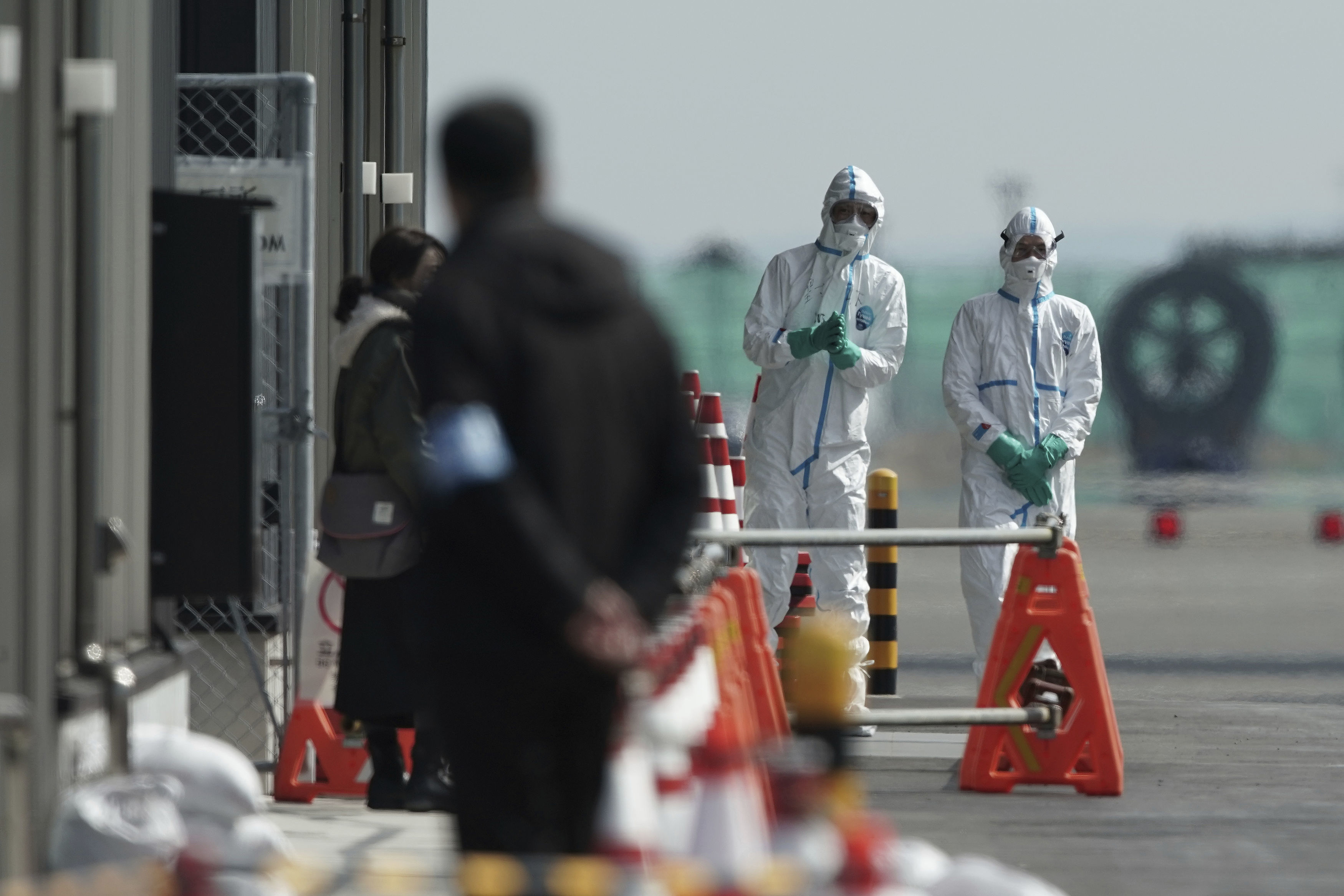 Officials in protective suits talk