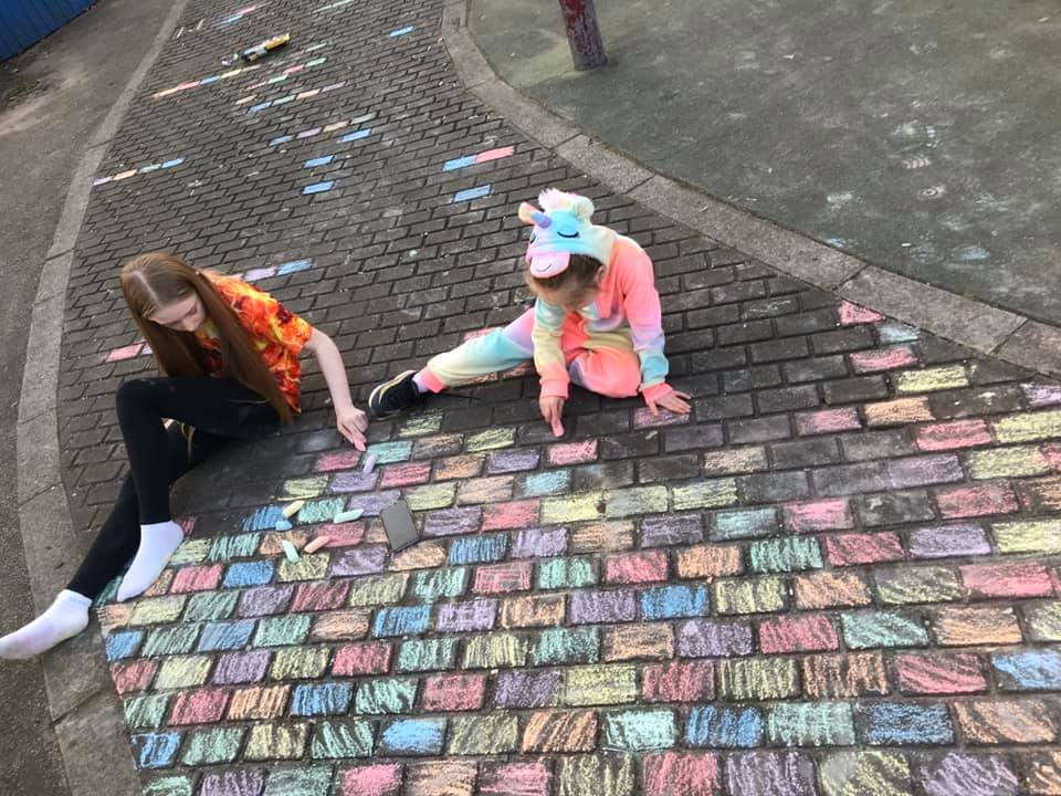 Two sisters have created a giant rainbow tribute to the NHS on their street in Manchester
