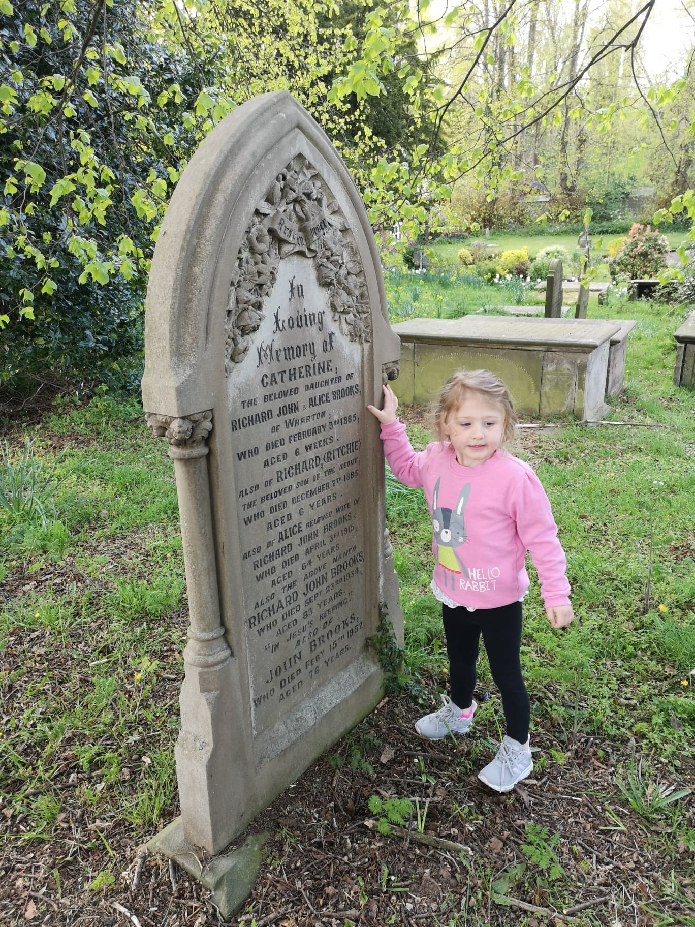 Lana stands with a cleaned up gravestone