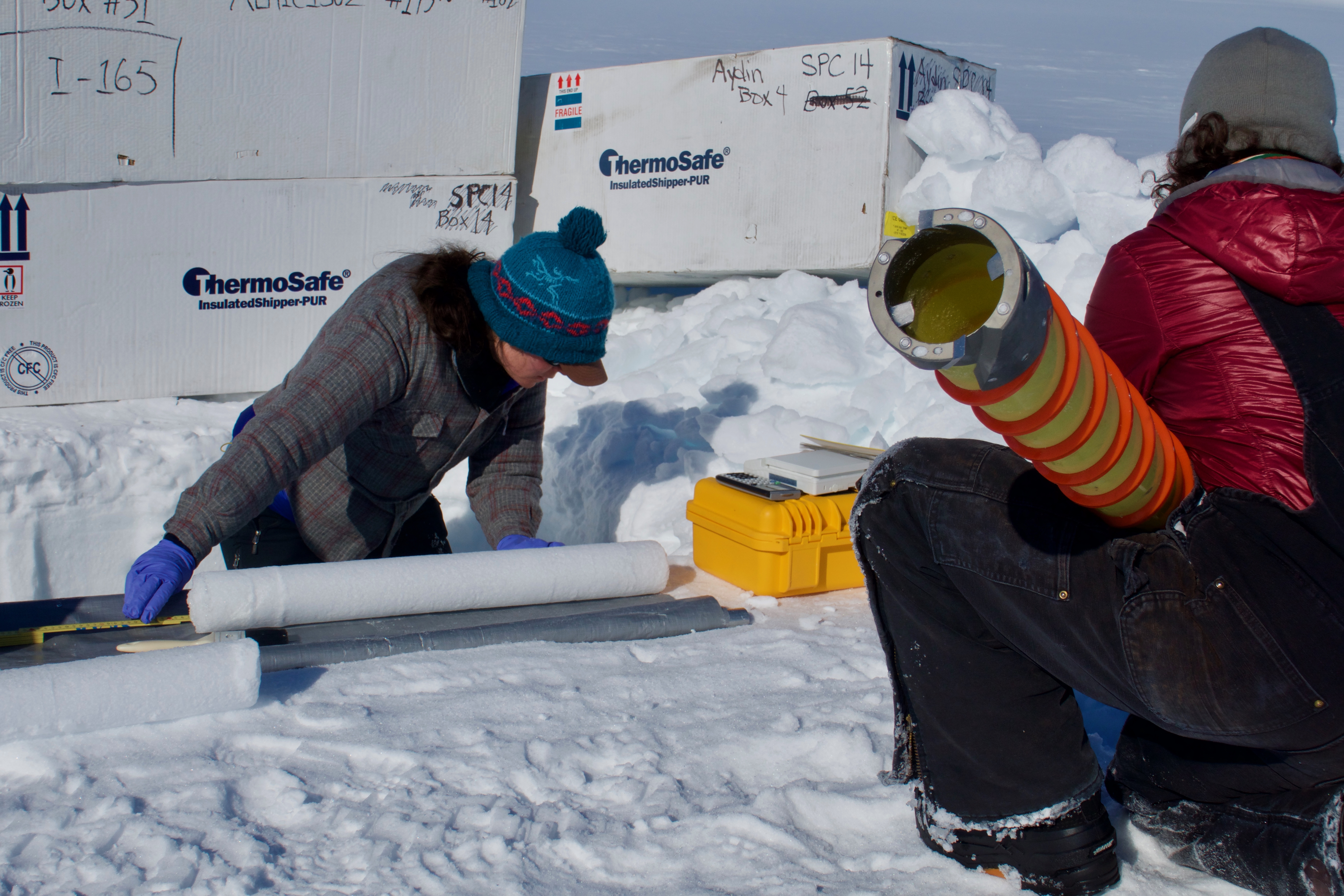 Researchers drill and measure ice cores in the Actic