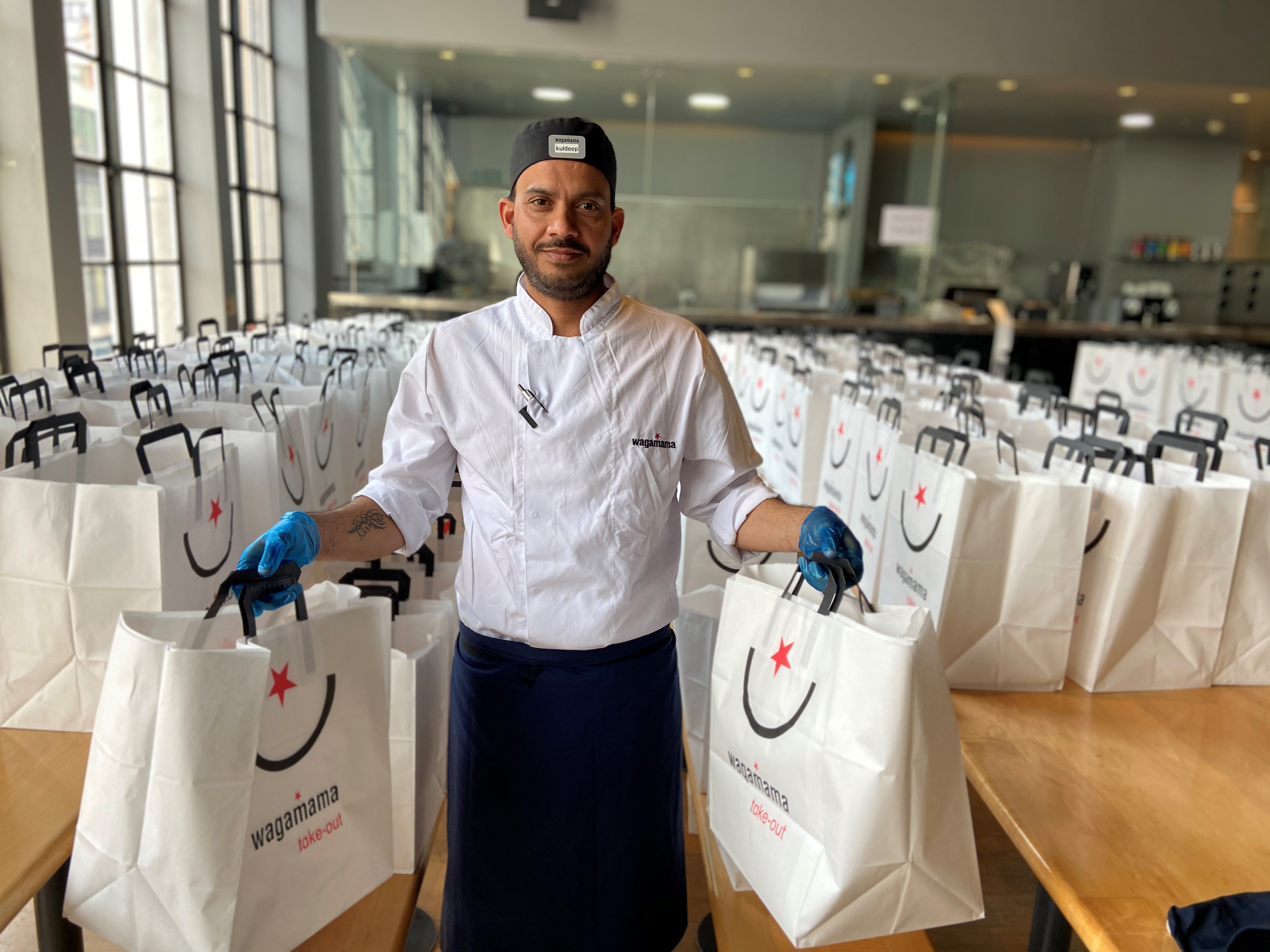 A Wagamama employee holding two takeaway bags
