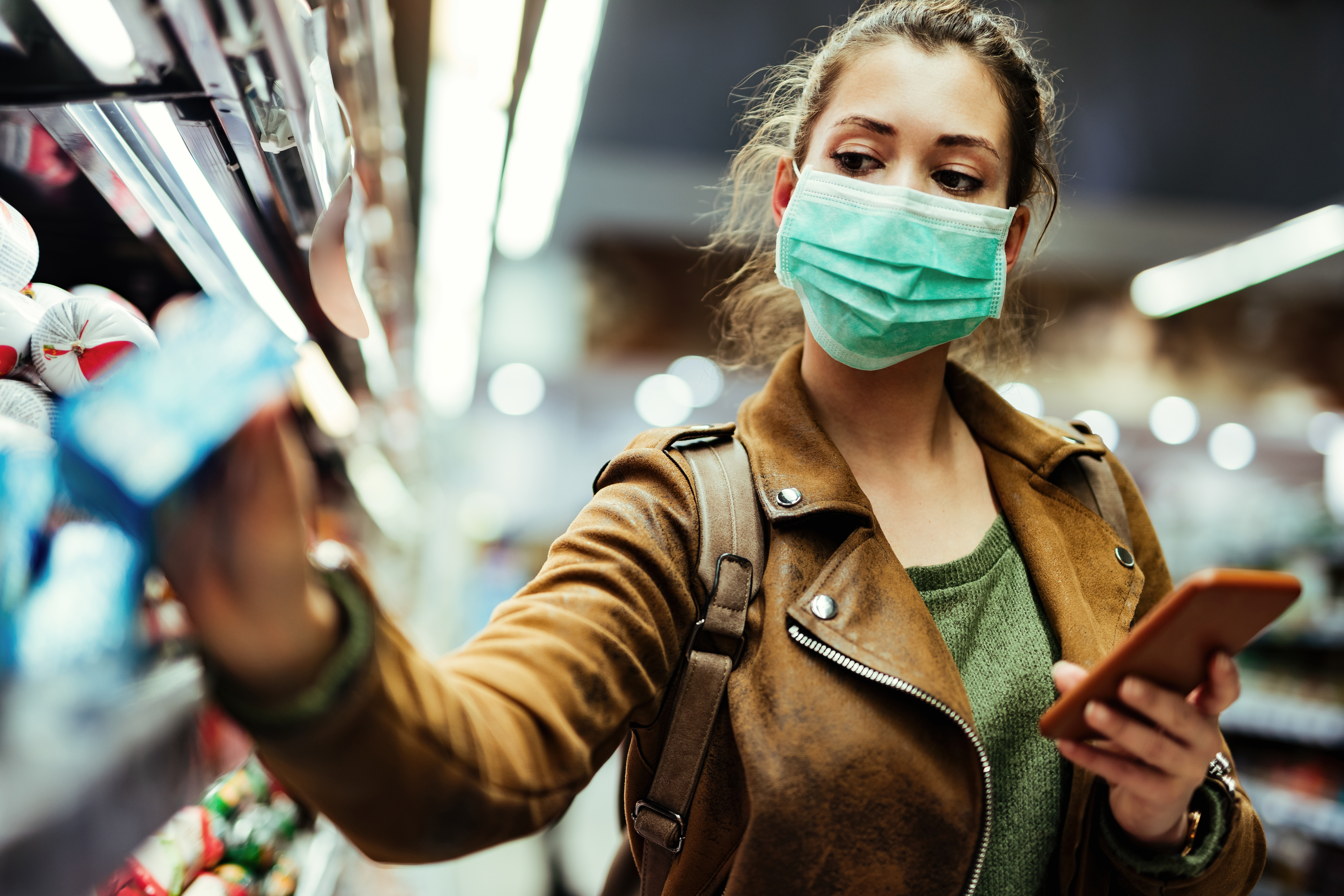 Woman wearing protective mask while using cell phone and buying food in grocery store