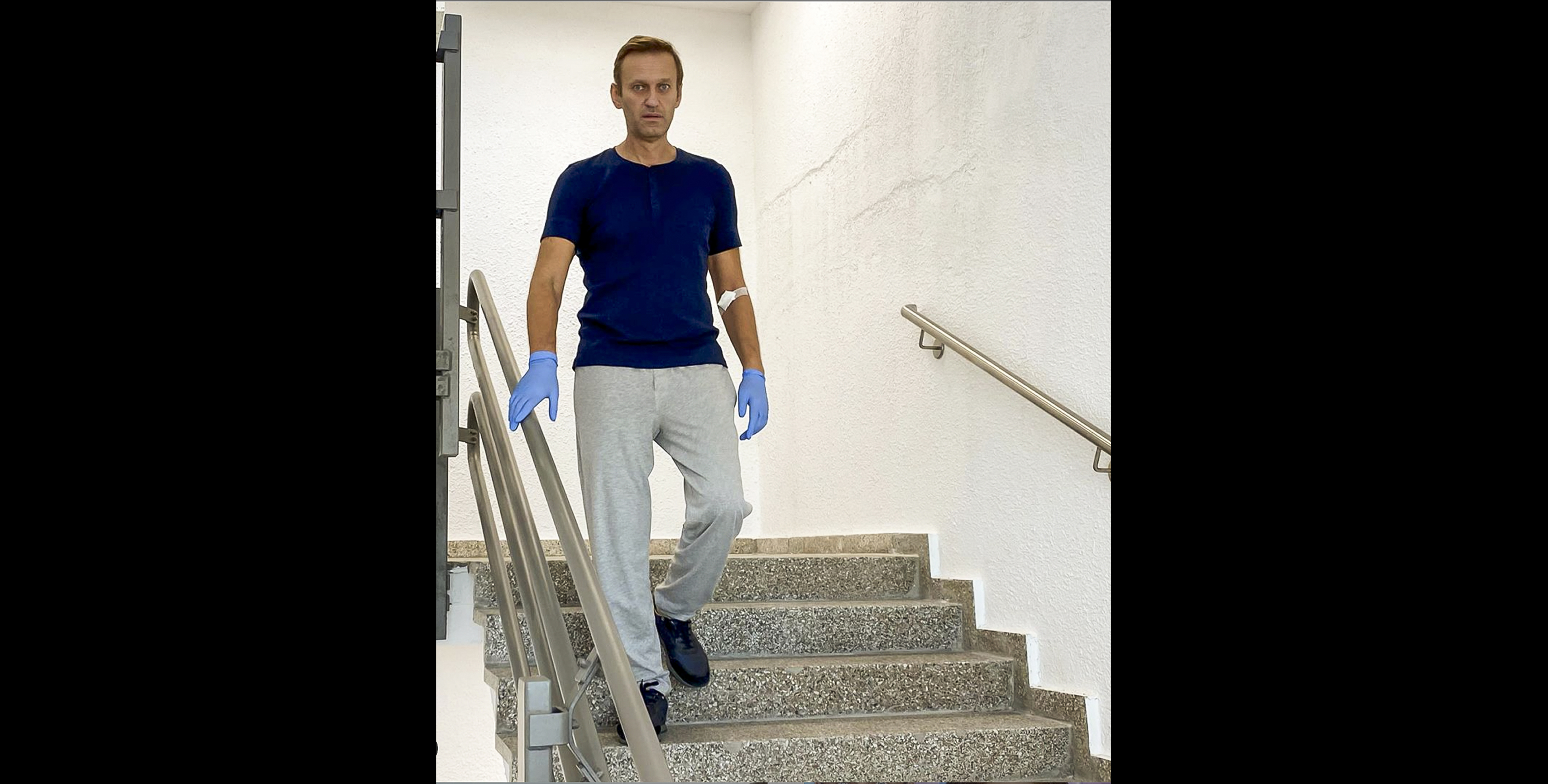 Russian opposition leader Alexei Navalny walks down stairs in a hospital in Berlin, Germany