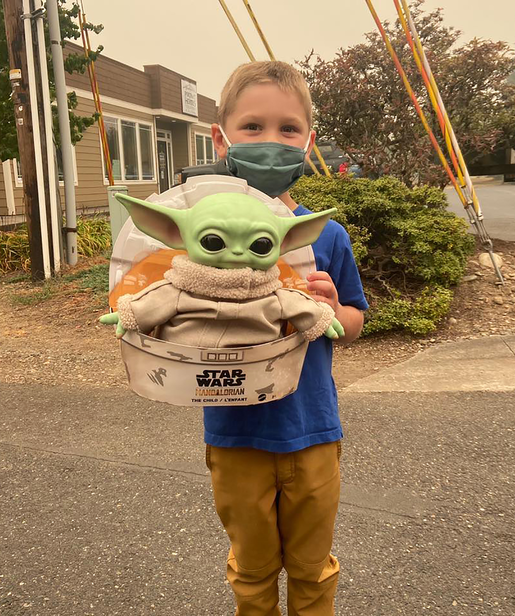 Five-year-old Carver holds up a Baby Yoda toy in Scappoose, Oregon