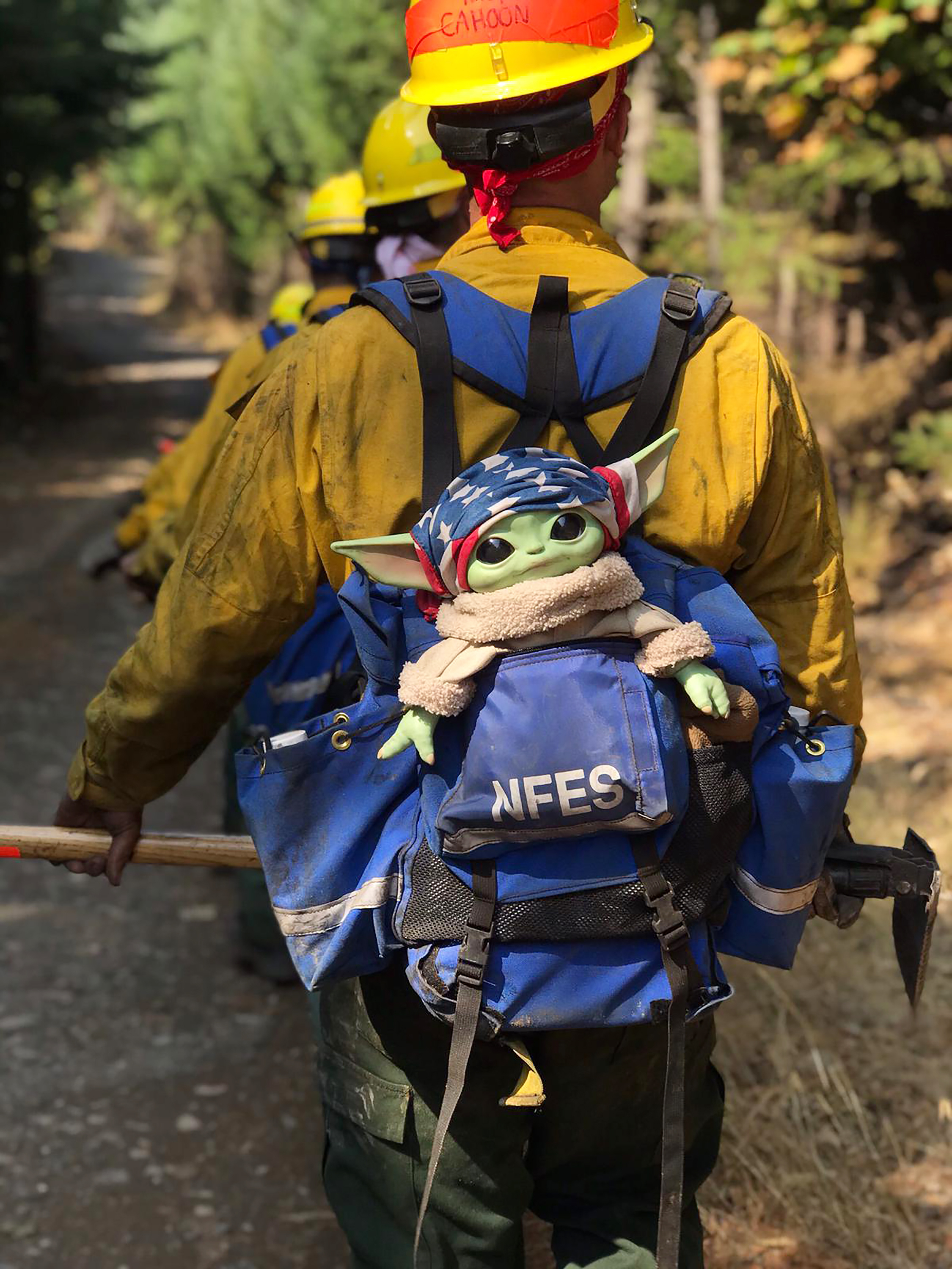 A Baby Yoda doll hitches a ride in the backpack of an Oregon Air National Guard firefighter