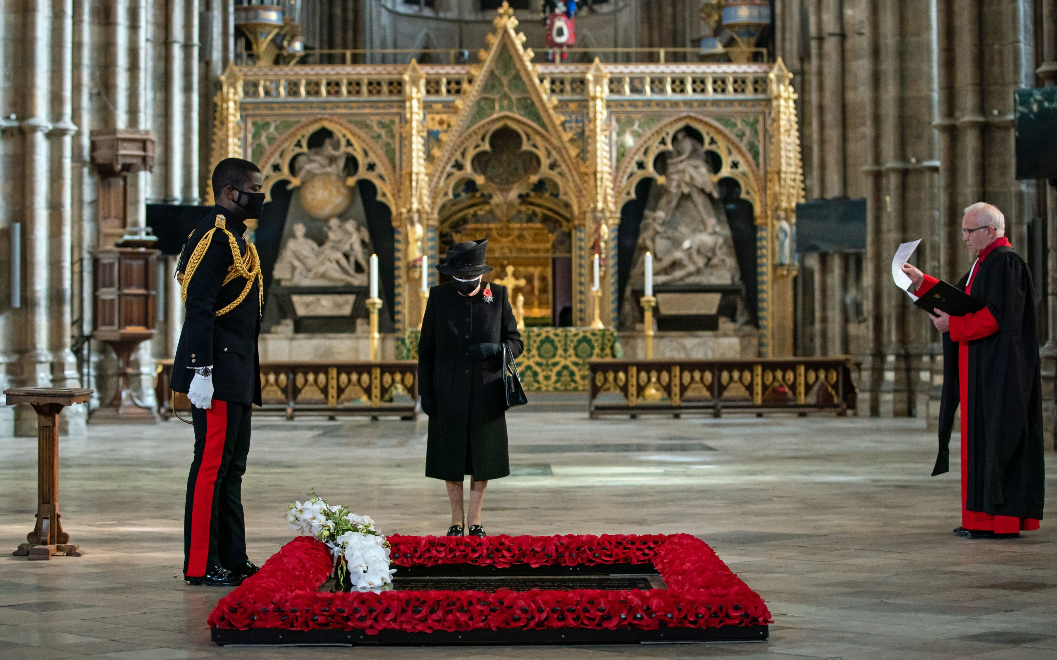The Dean of Westminster Dr David Hoyle (right) watches as the flowers are placed on the tomb