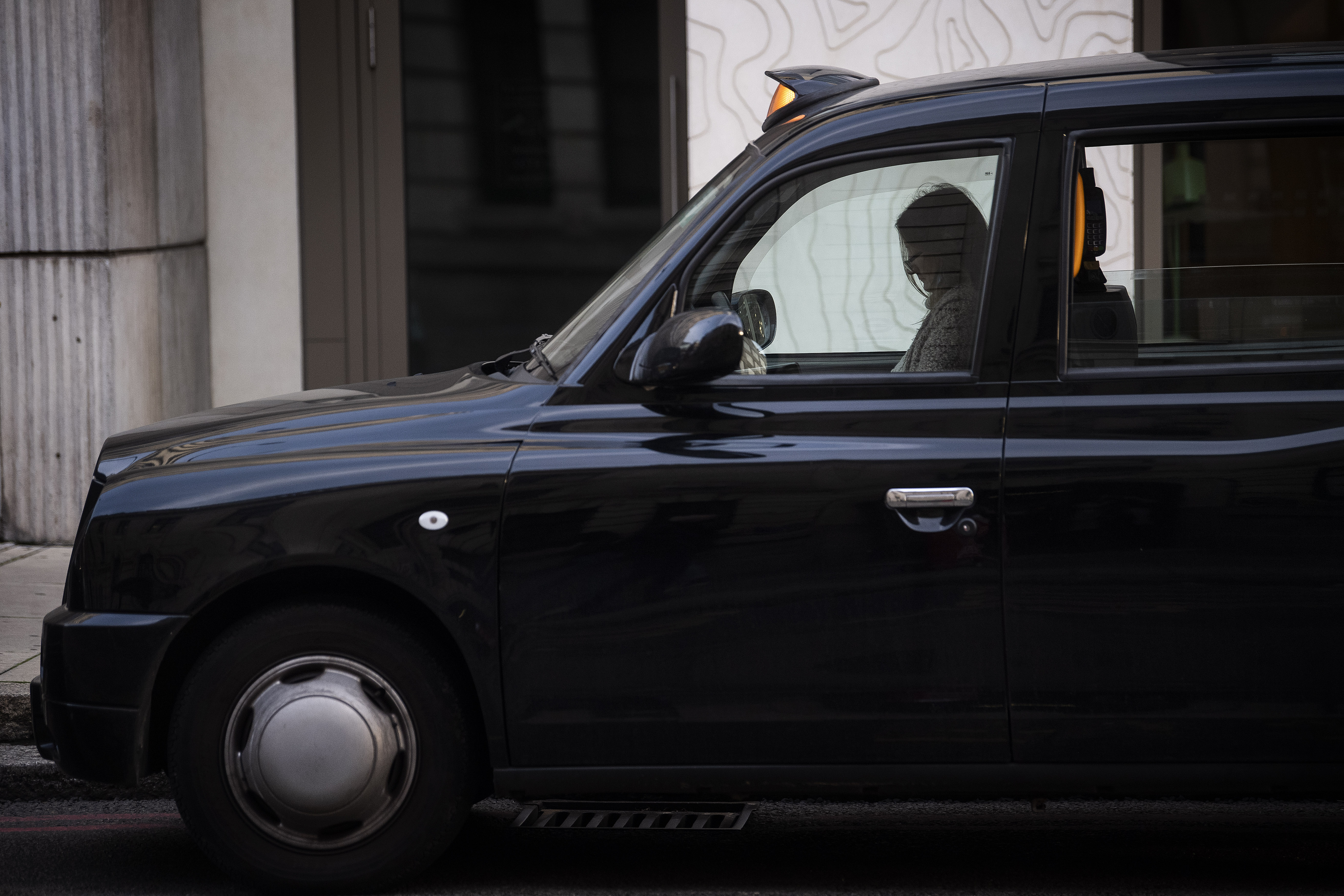 A driver seemingly asleep in a black cab queuing for a fare outside London Victoria railway station (Victoria Jones/PA)