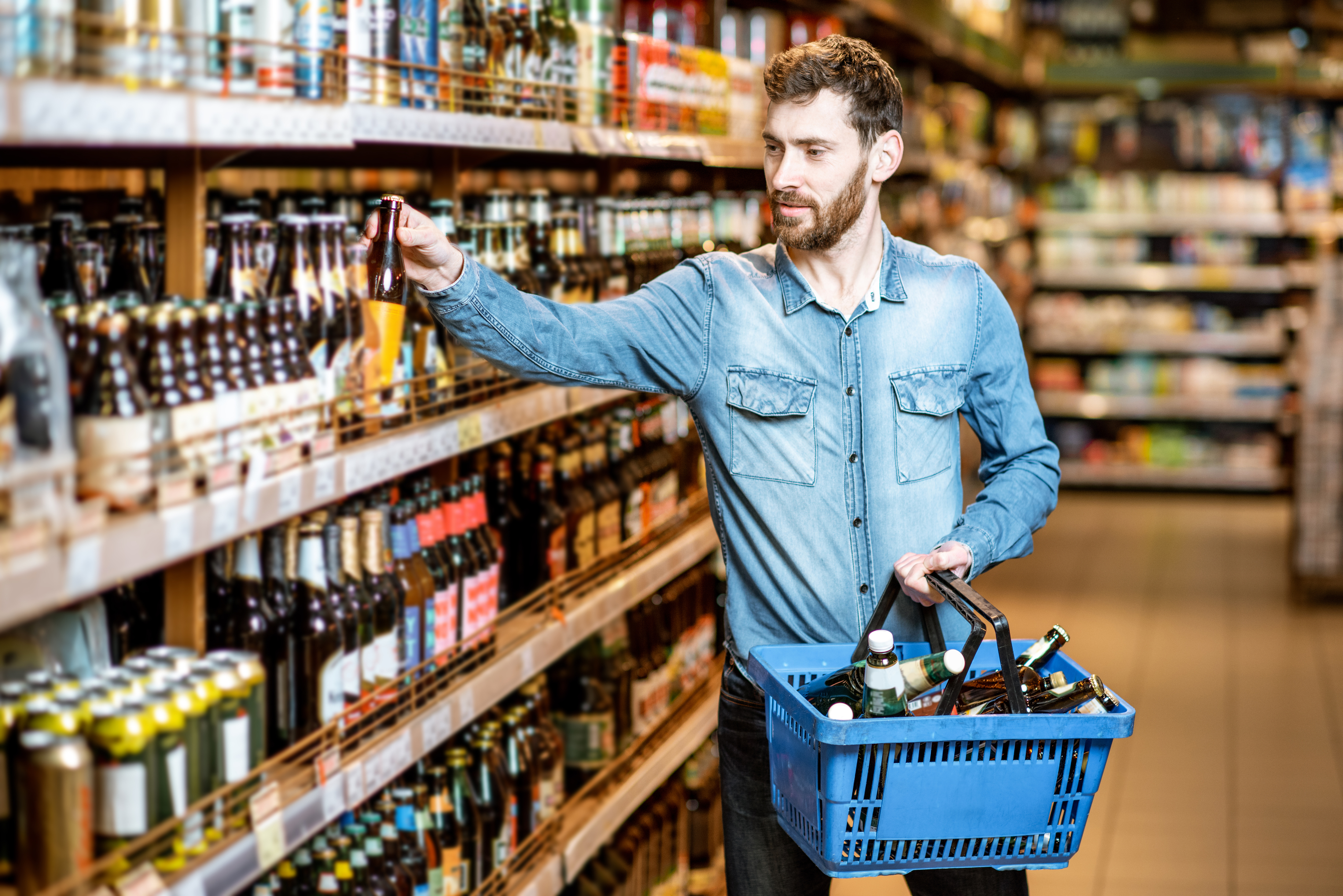 Man buying beer in the supermarket without a mask