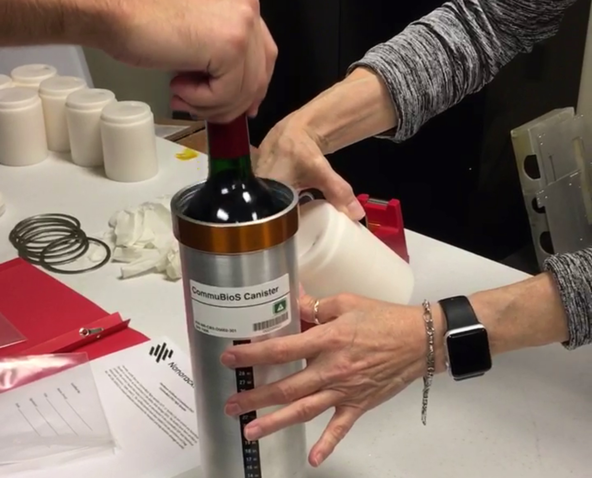 Researchers from the company prepare bottles of French red wine to be flown from Wallops Island to the International Space Station