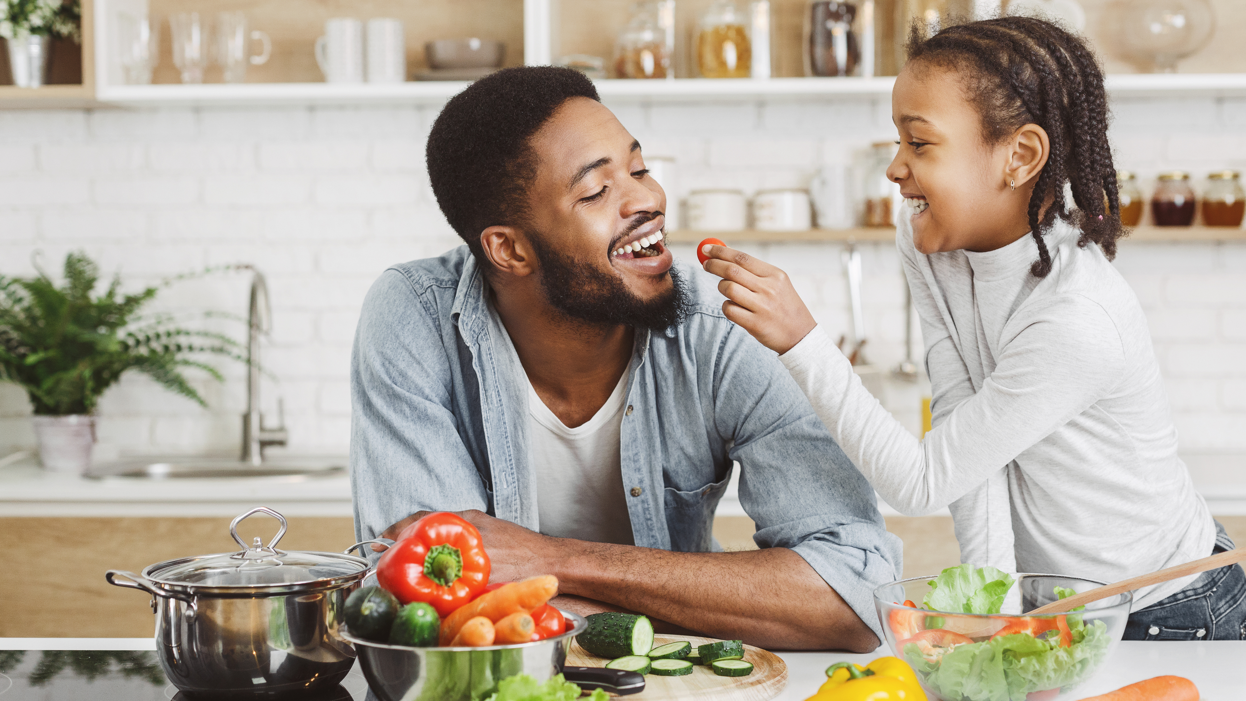 A father and young daughter having fun in the kitchen preparing healthy plant-based food