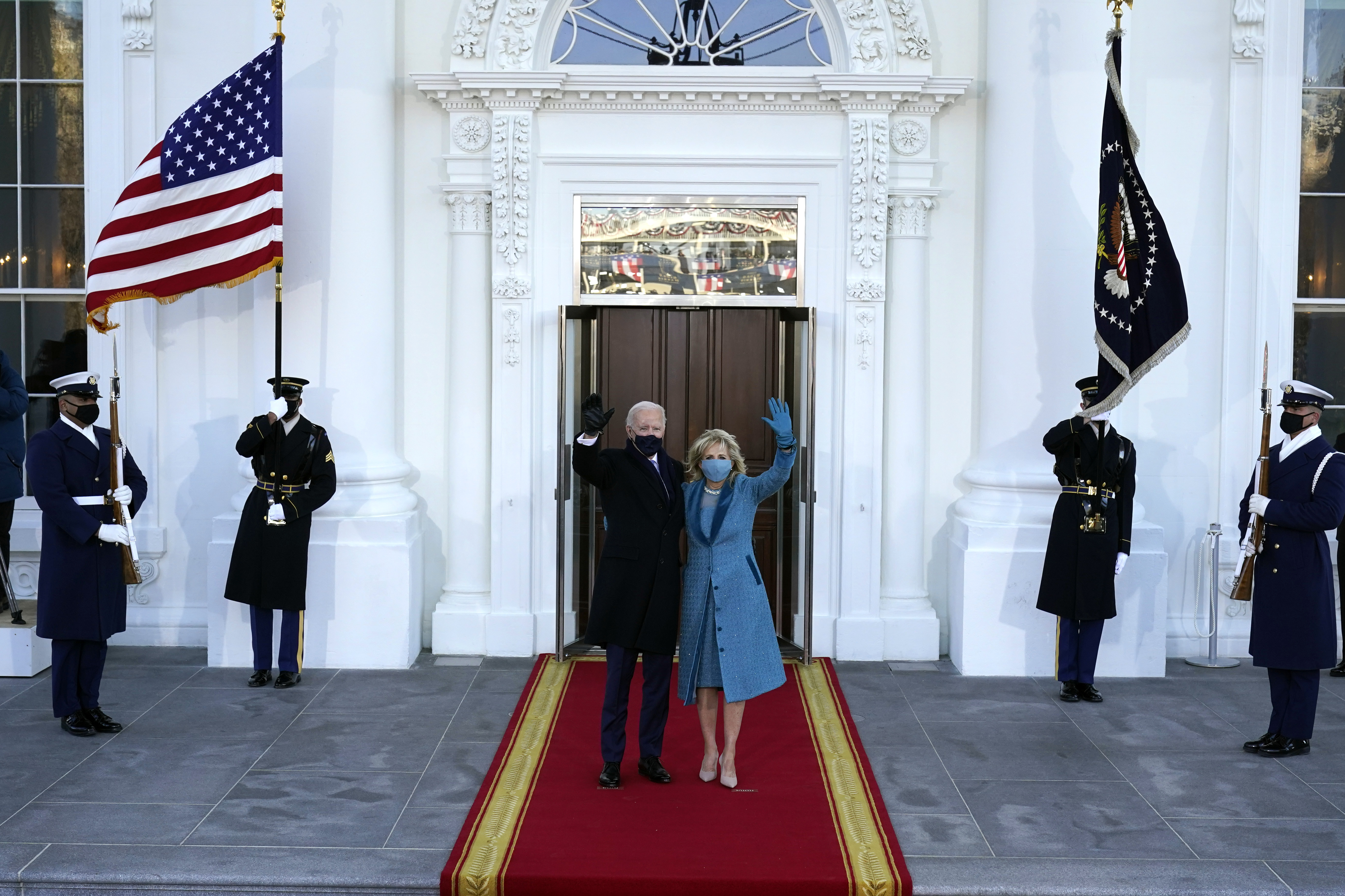 President Joe Biden and first lady Jill Biden wave as they arrive at the North Portico of the White House