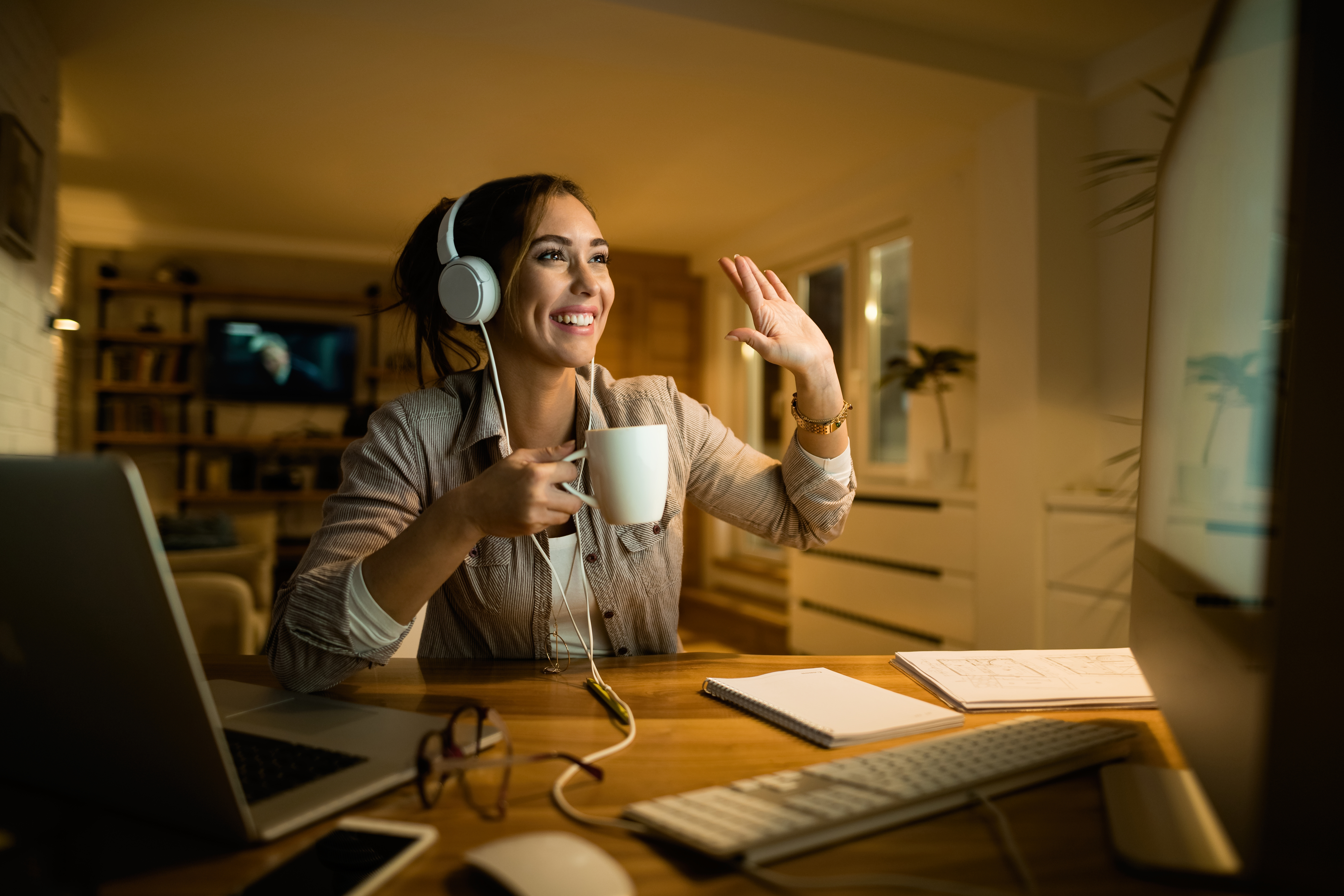 Happy woman with headphones making video call over computer at night.