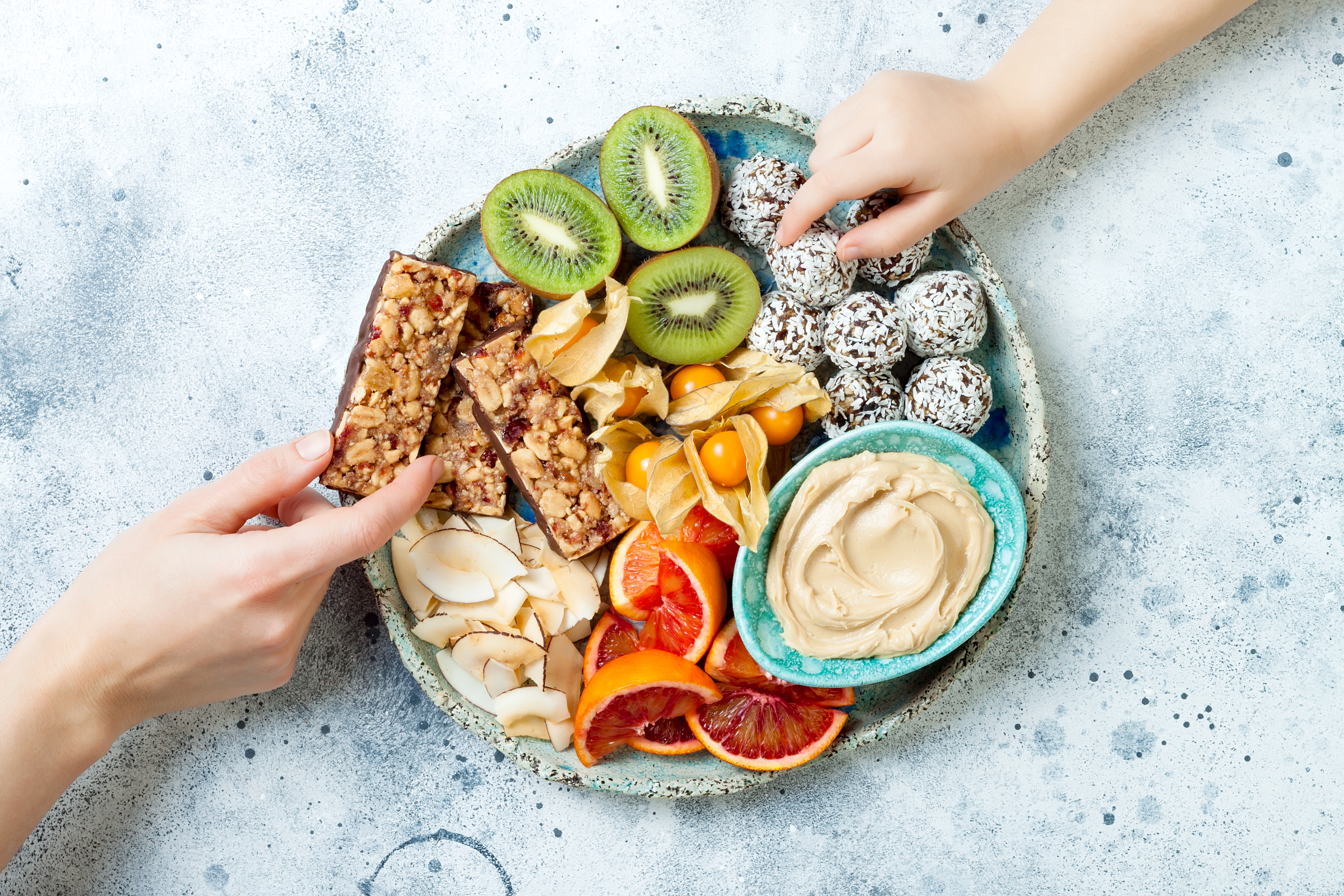Mother giving healthy vegan dessert snacks to toddler child. Concept of healthy sweets for children. Protein granola bars, homemade raw energy balls, cashew butter, toasted coconut chips, fruits platter