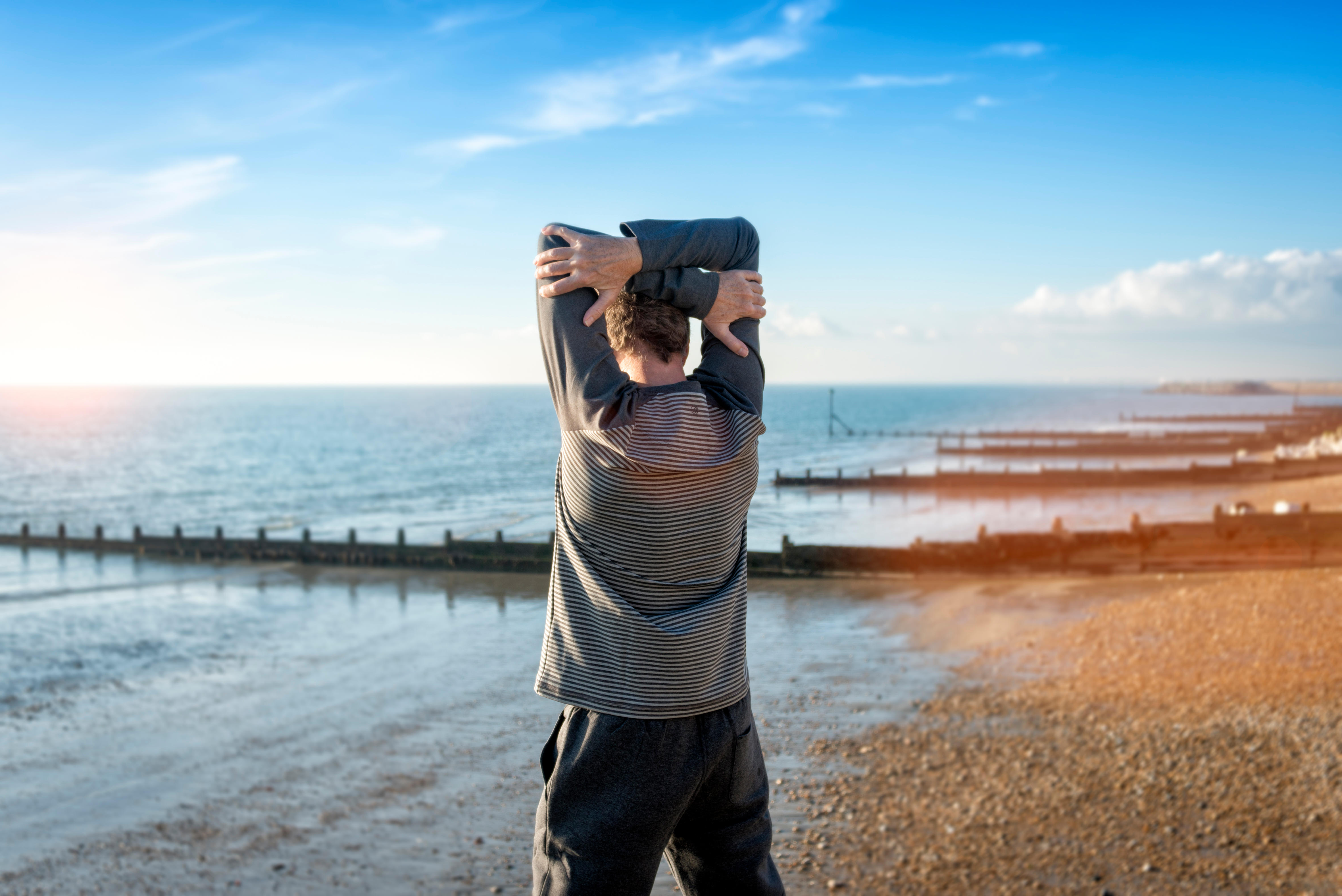 man stretching by the sea, warming up before exercise training.