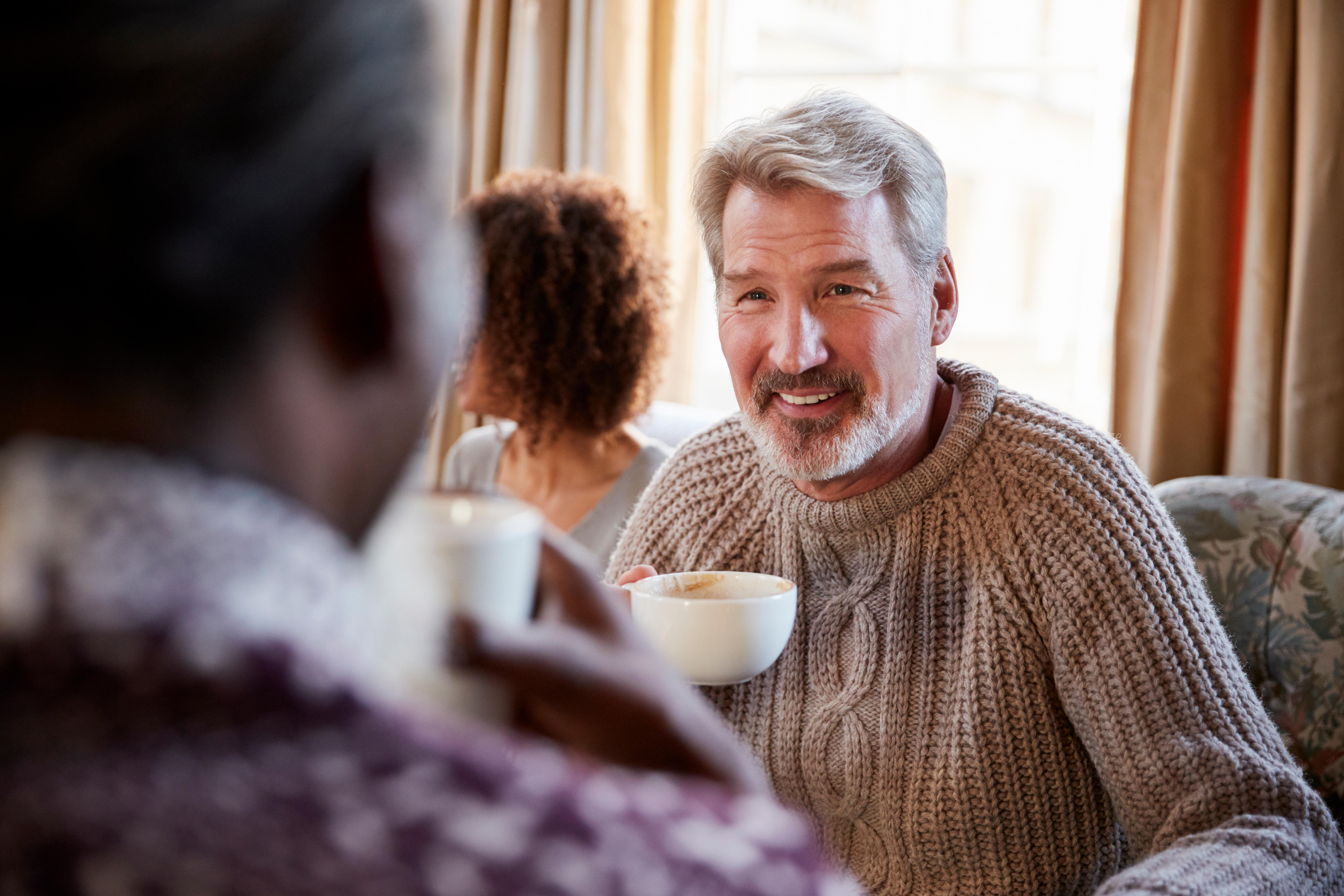 Mature man drinking coffee with a friend