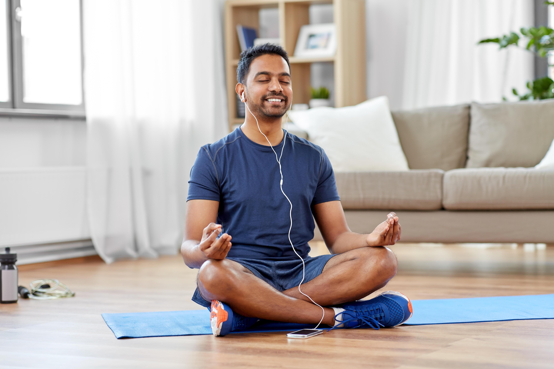 man meditating in lotus pose at home