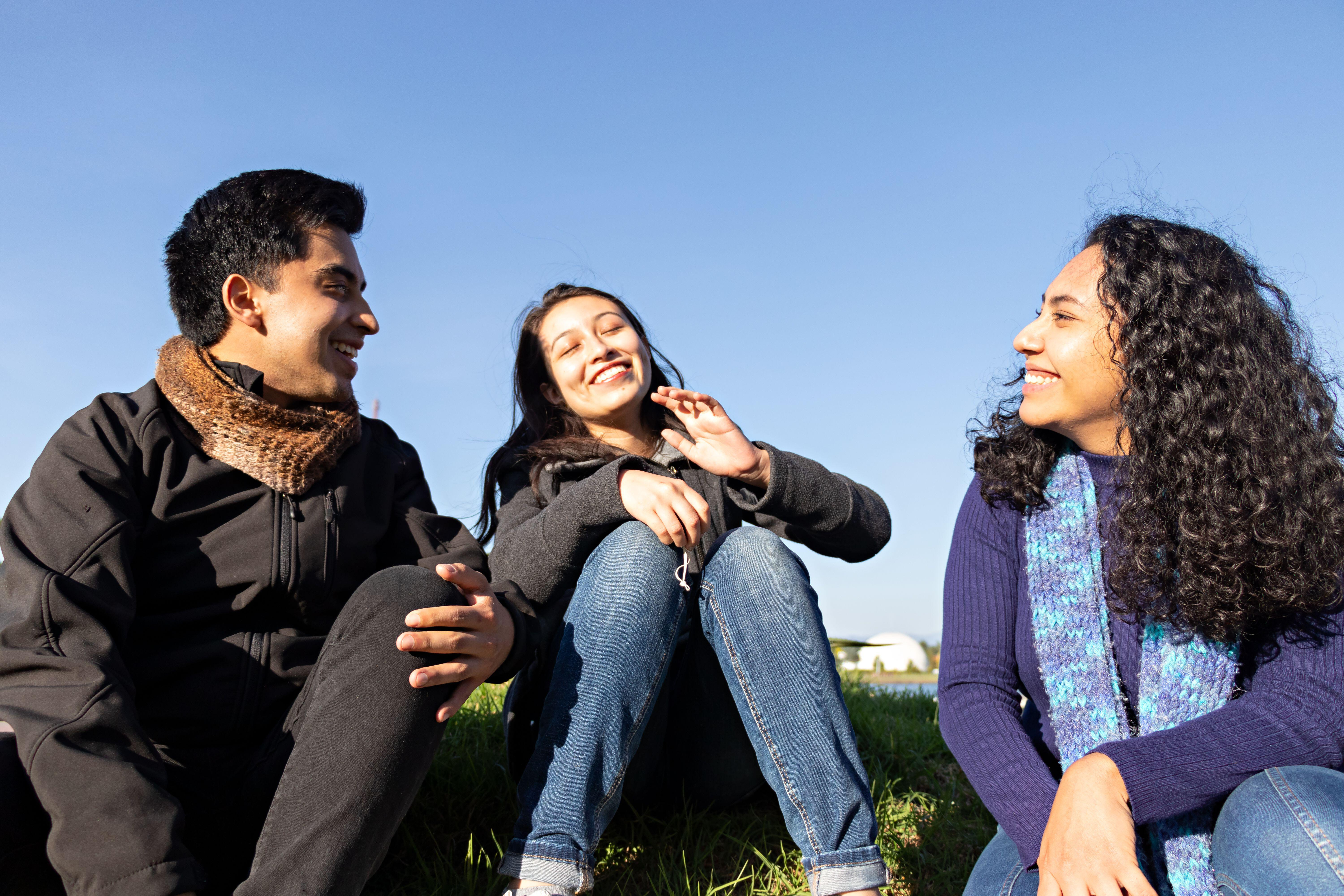 group of friends, two women and a man, talking and laughing