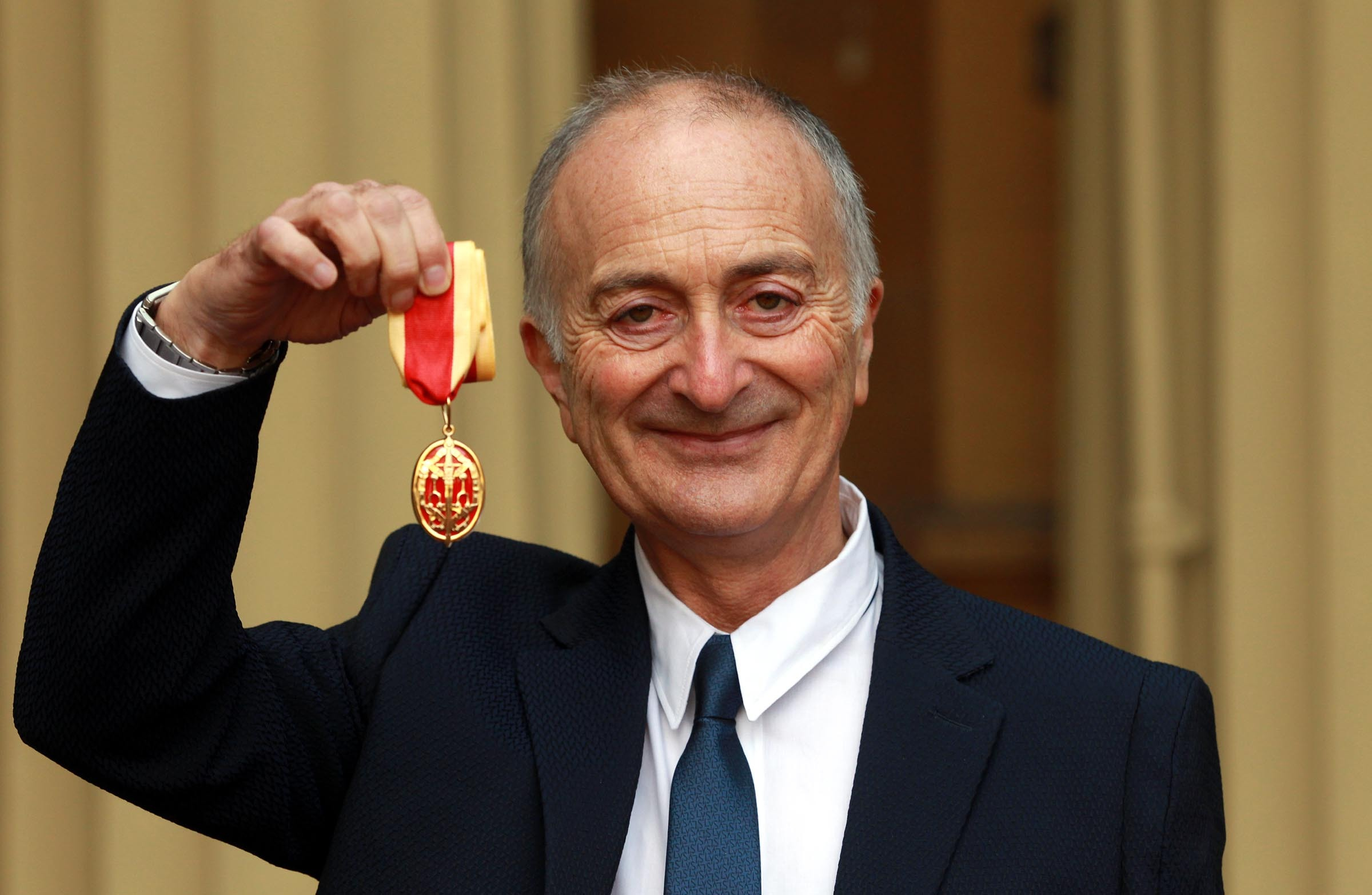 Sir Tony Robinson holds his medal after being knighted in 2013