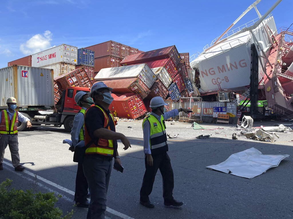 Port workers watch the scene after the crane overturns