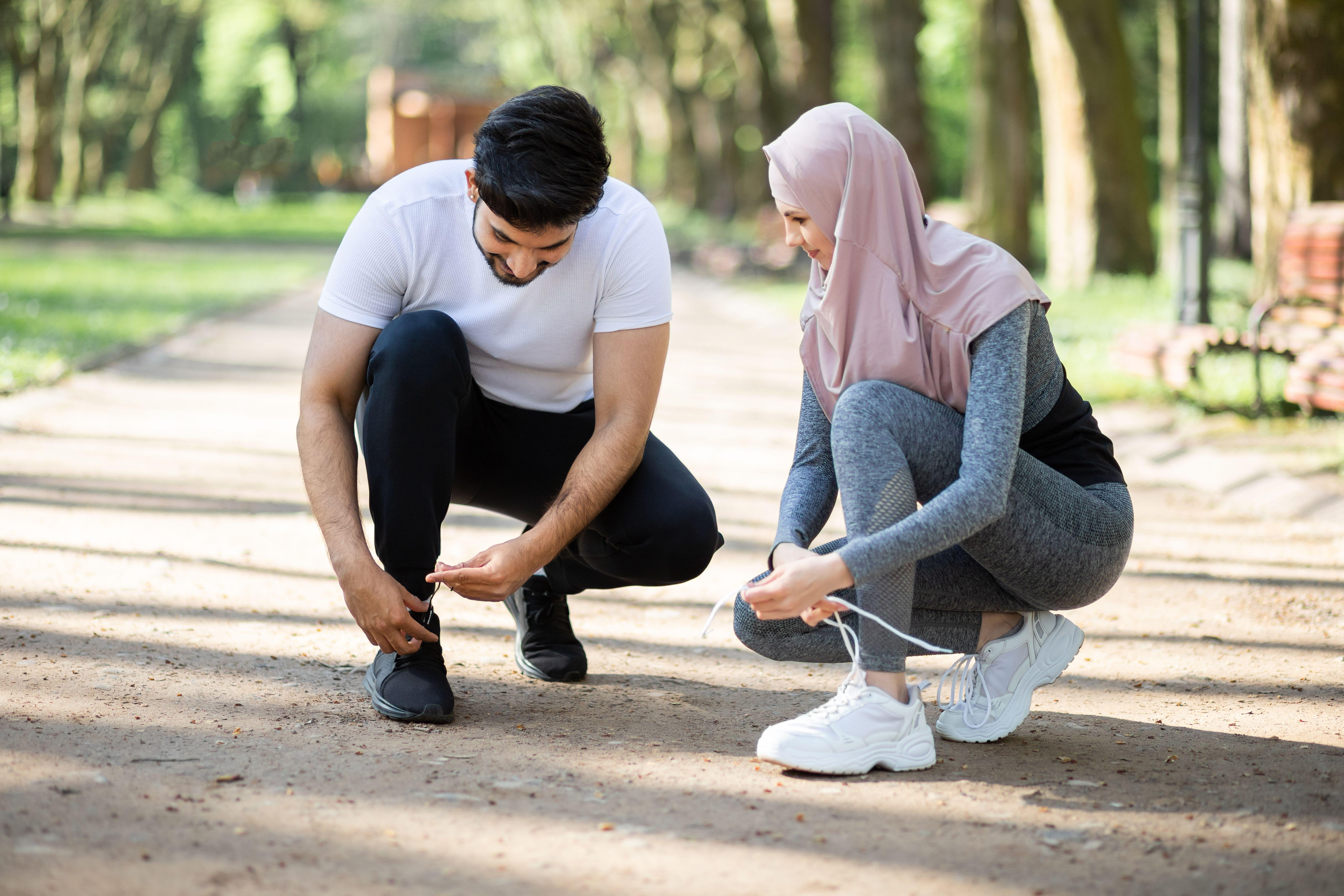 Muslim man and woman in hijab tying laces on sport sneakers before morning run at green park. Young active family training together on fresh air.