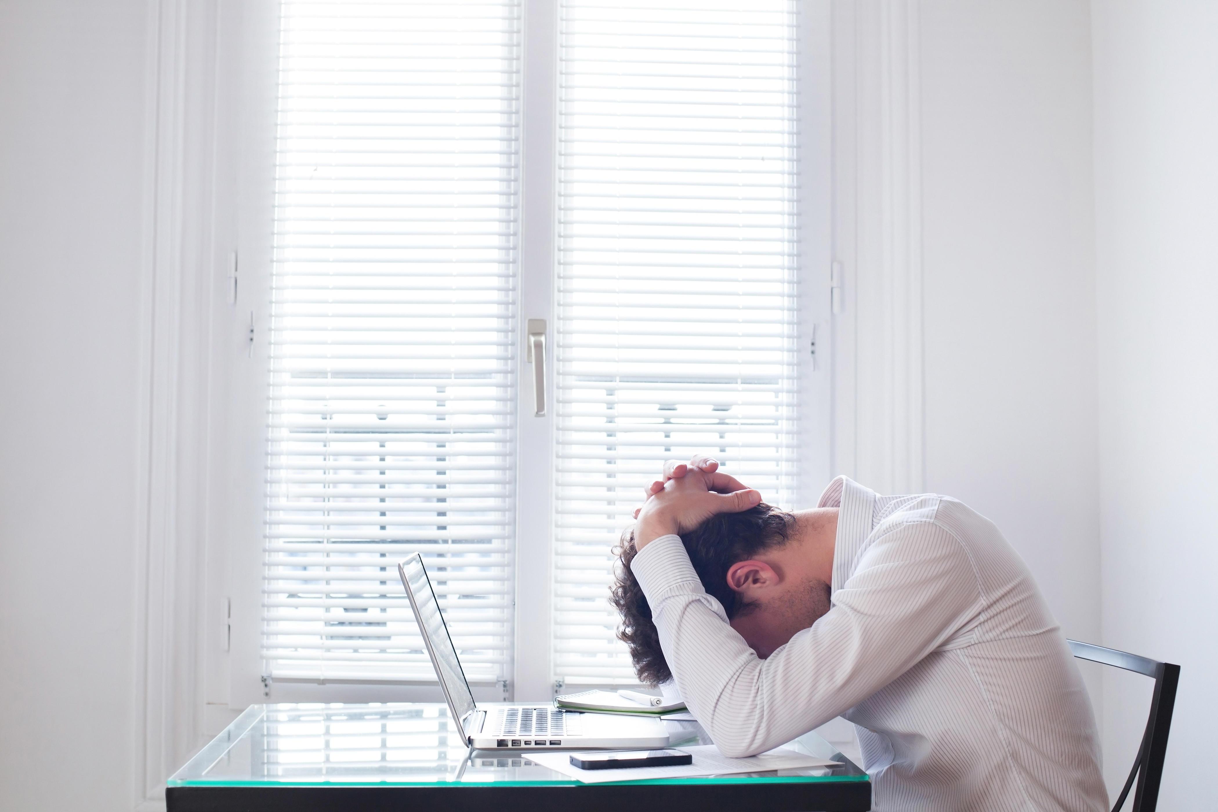 Stressed man at work (Alamy/PA)