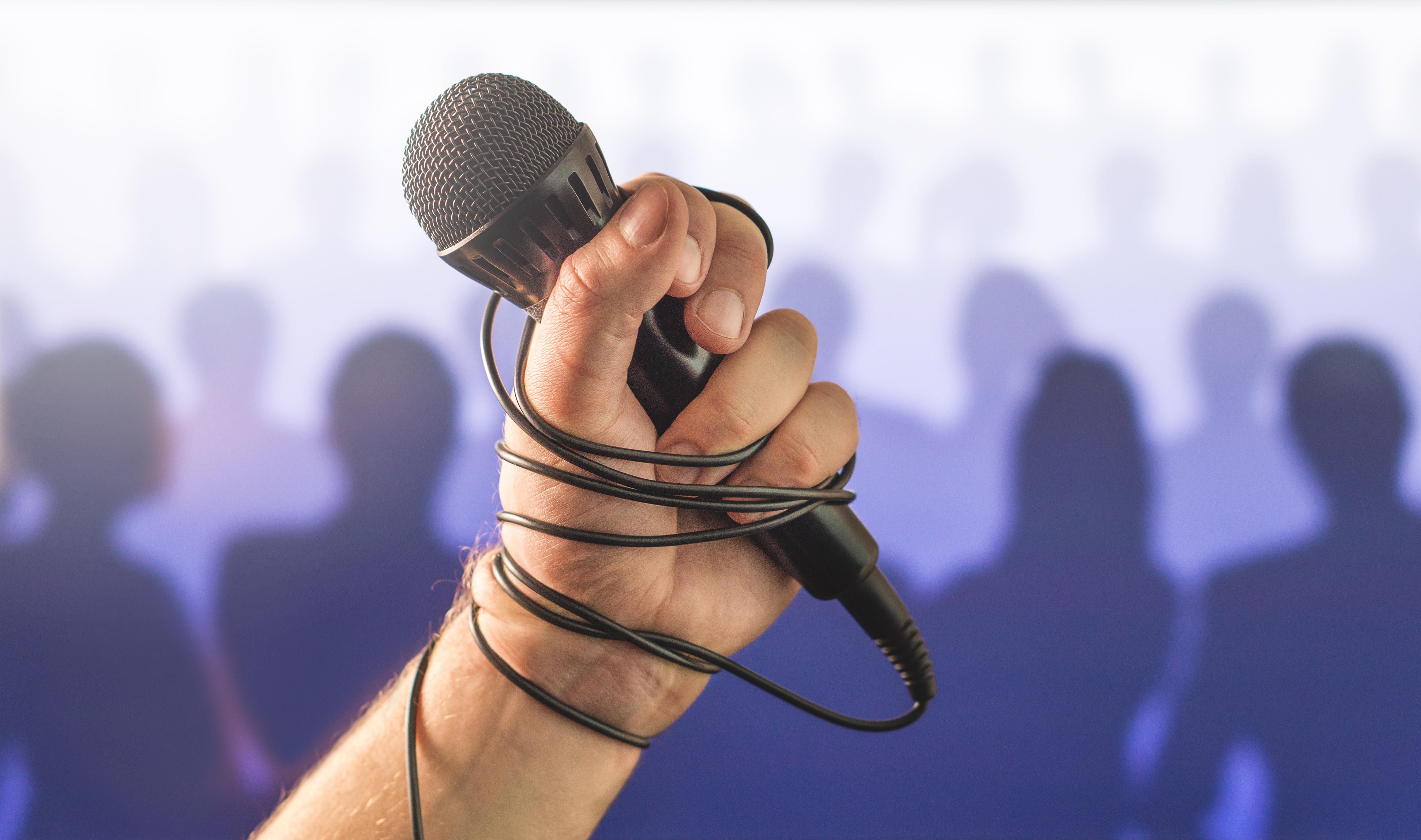 Stage fright in public speaking or bad karaoke singing live in front of crowd of people. Problem with speech or failed talent show performance.