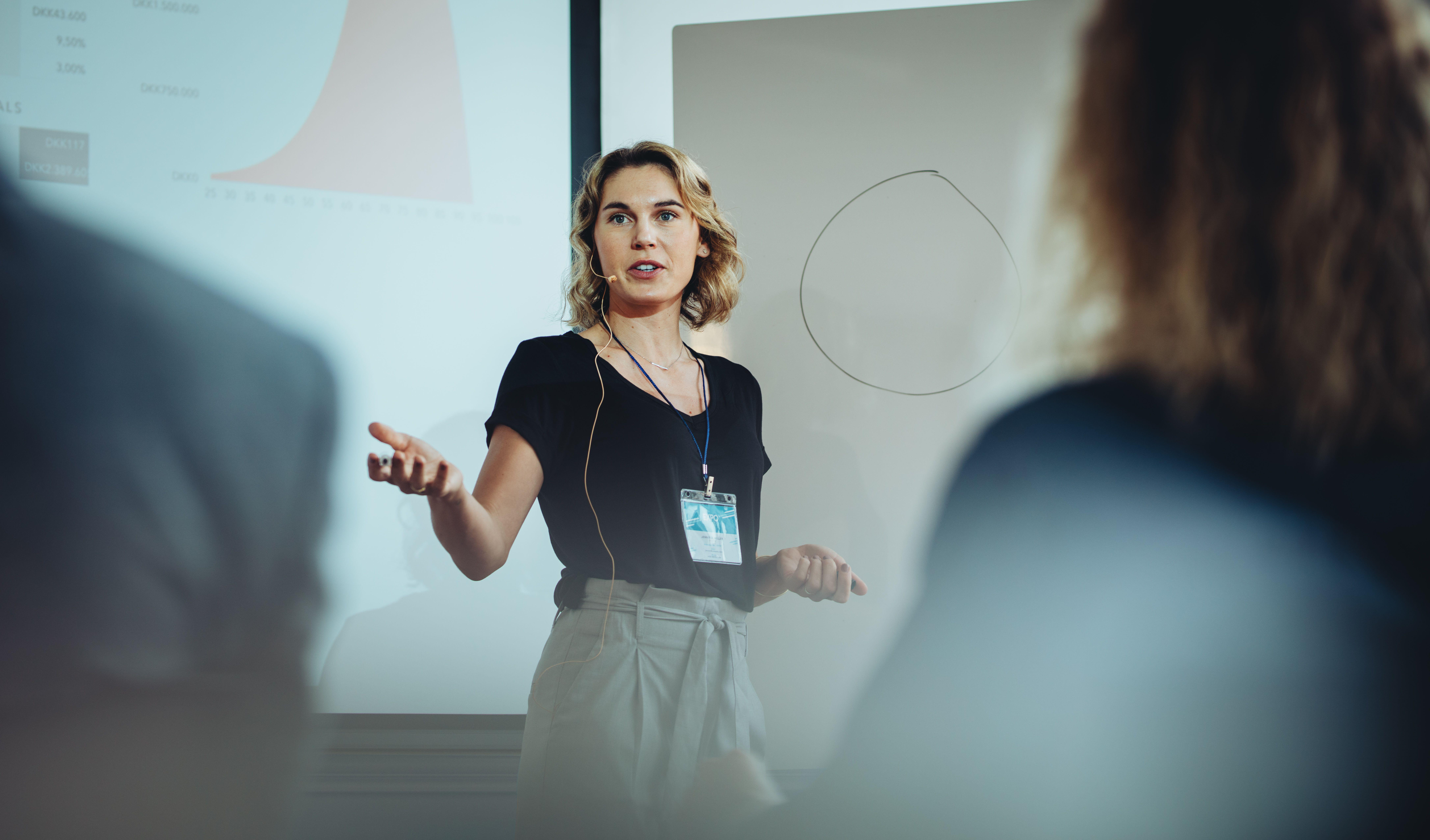 Woman presenting her idea to colleagues in meeting. Businesswoman public speaking in a conference meeting.