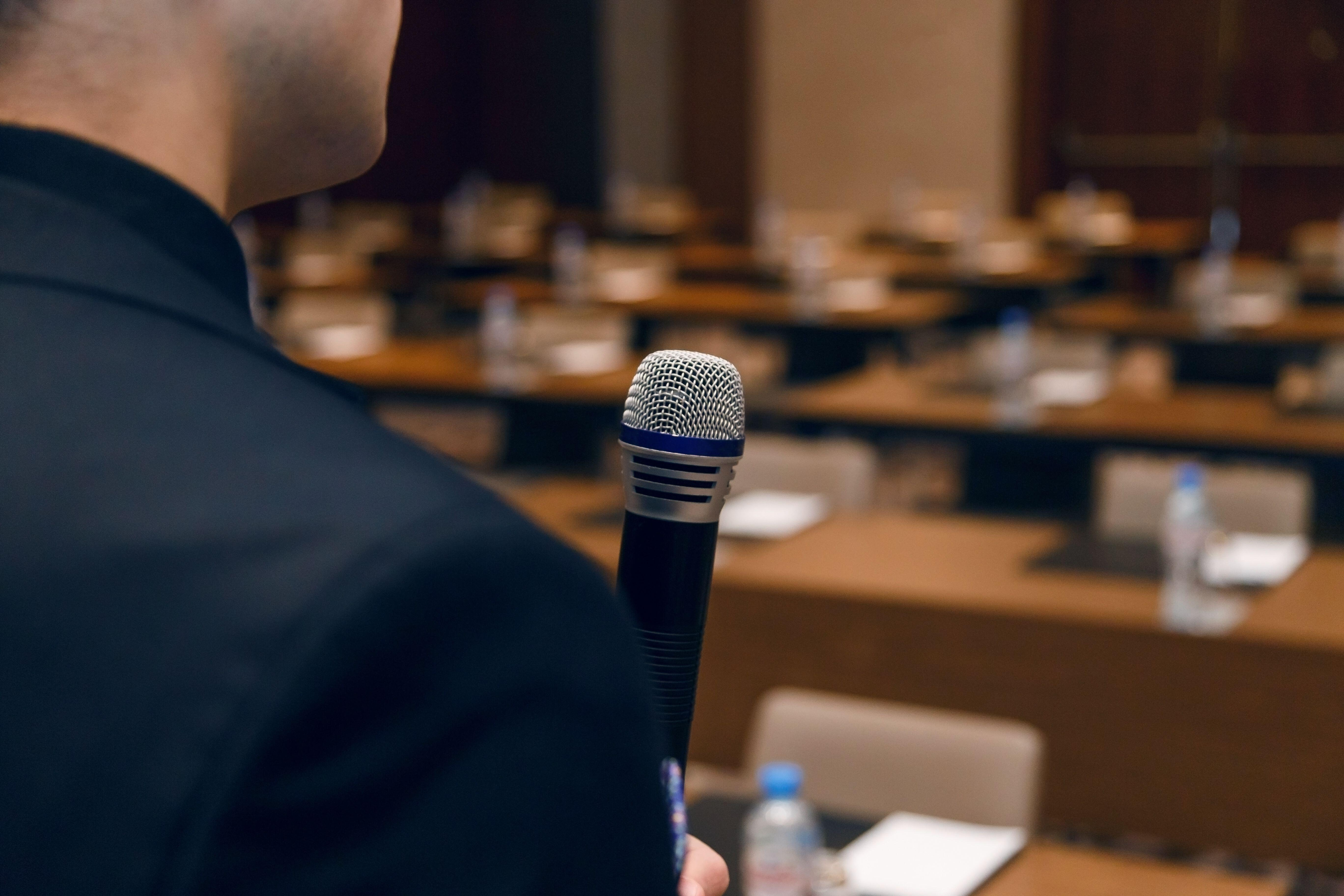 Microphone in hand of man in suit on background of empty conference hall. Rehearsal of public speaking