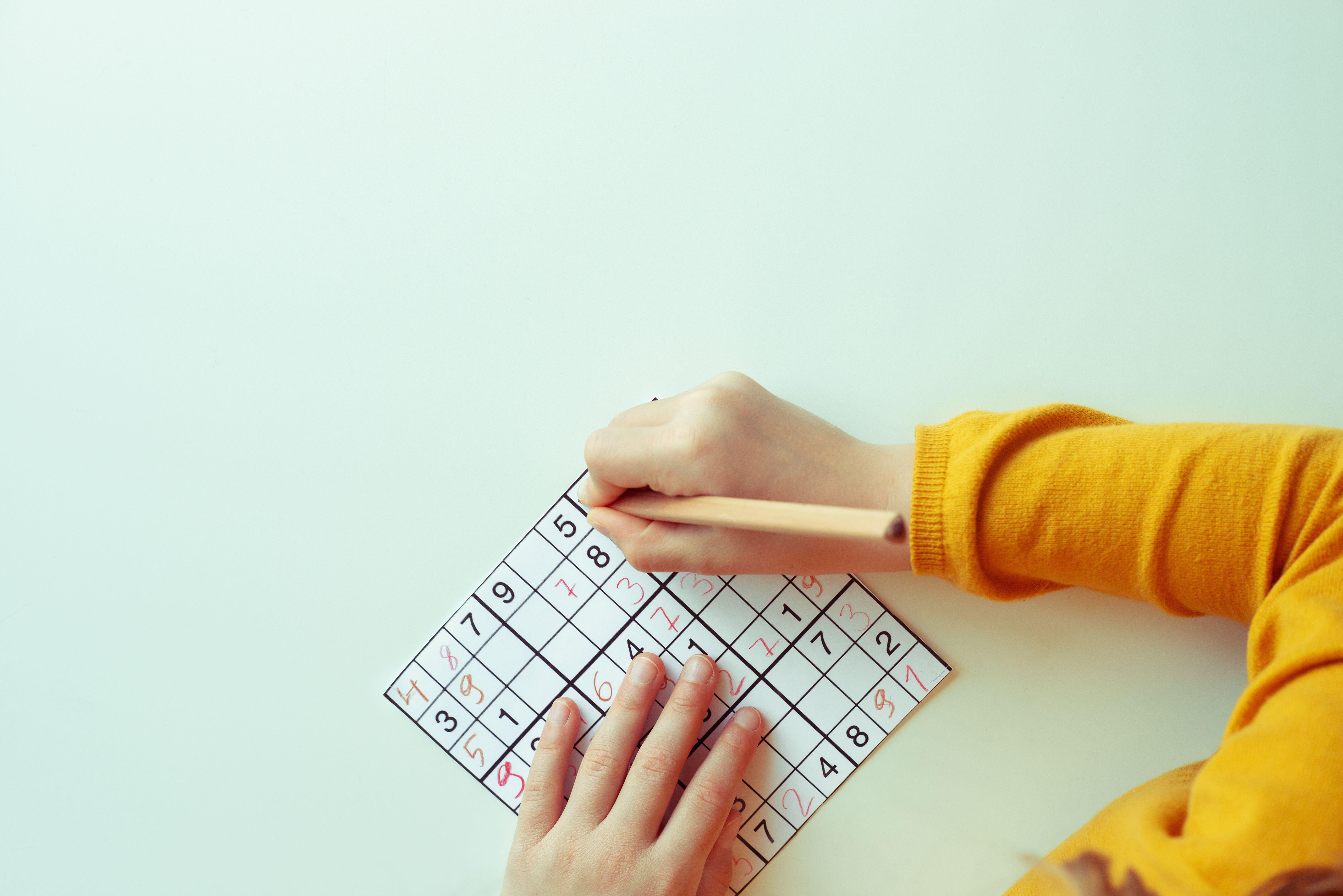 Person doing a sudoku puzzle