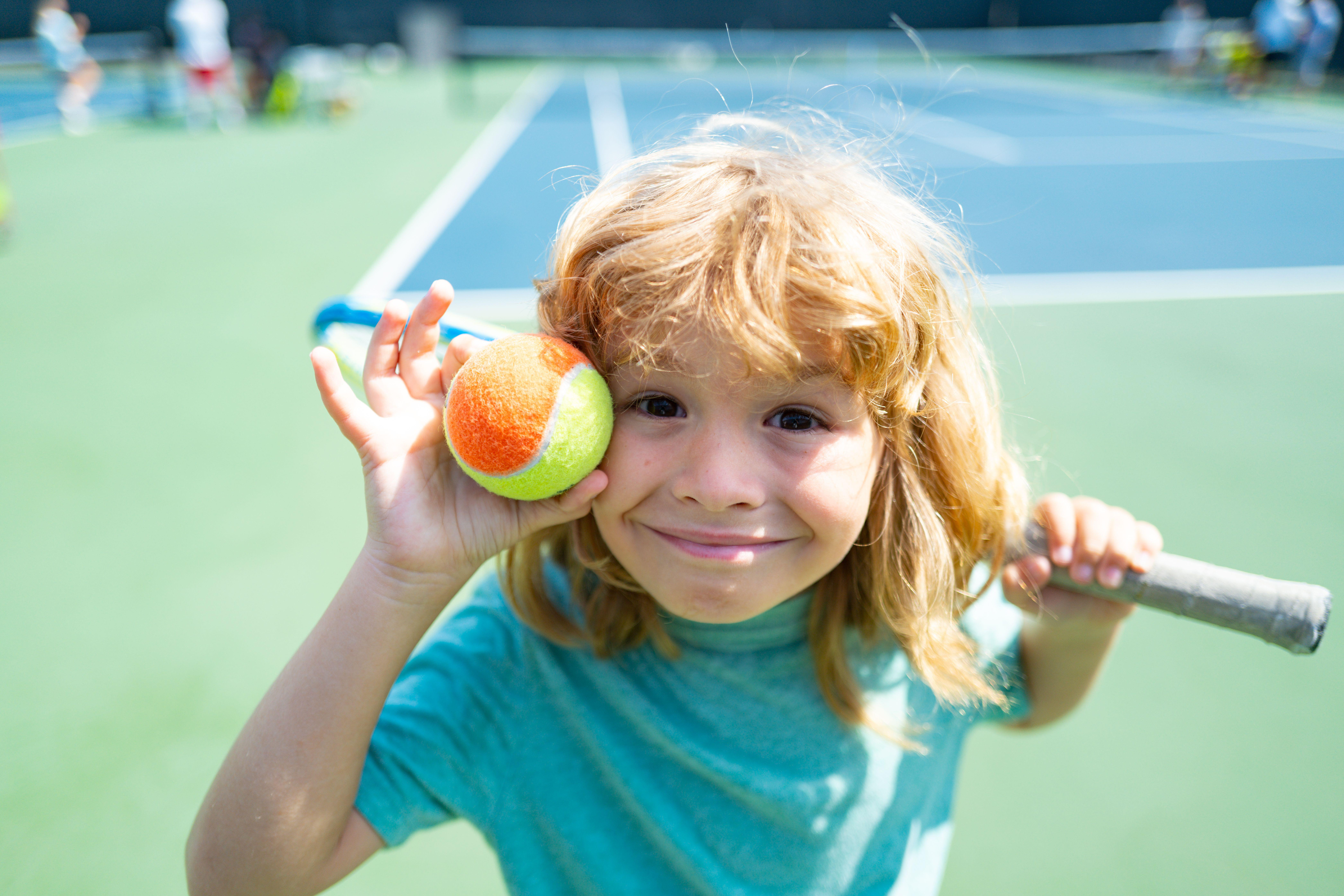 Child with tennis ball and racket