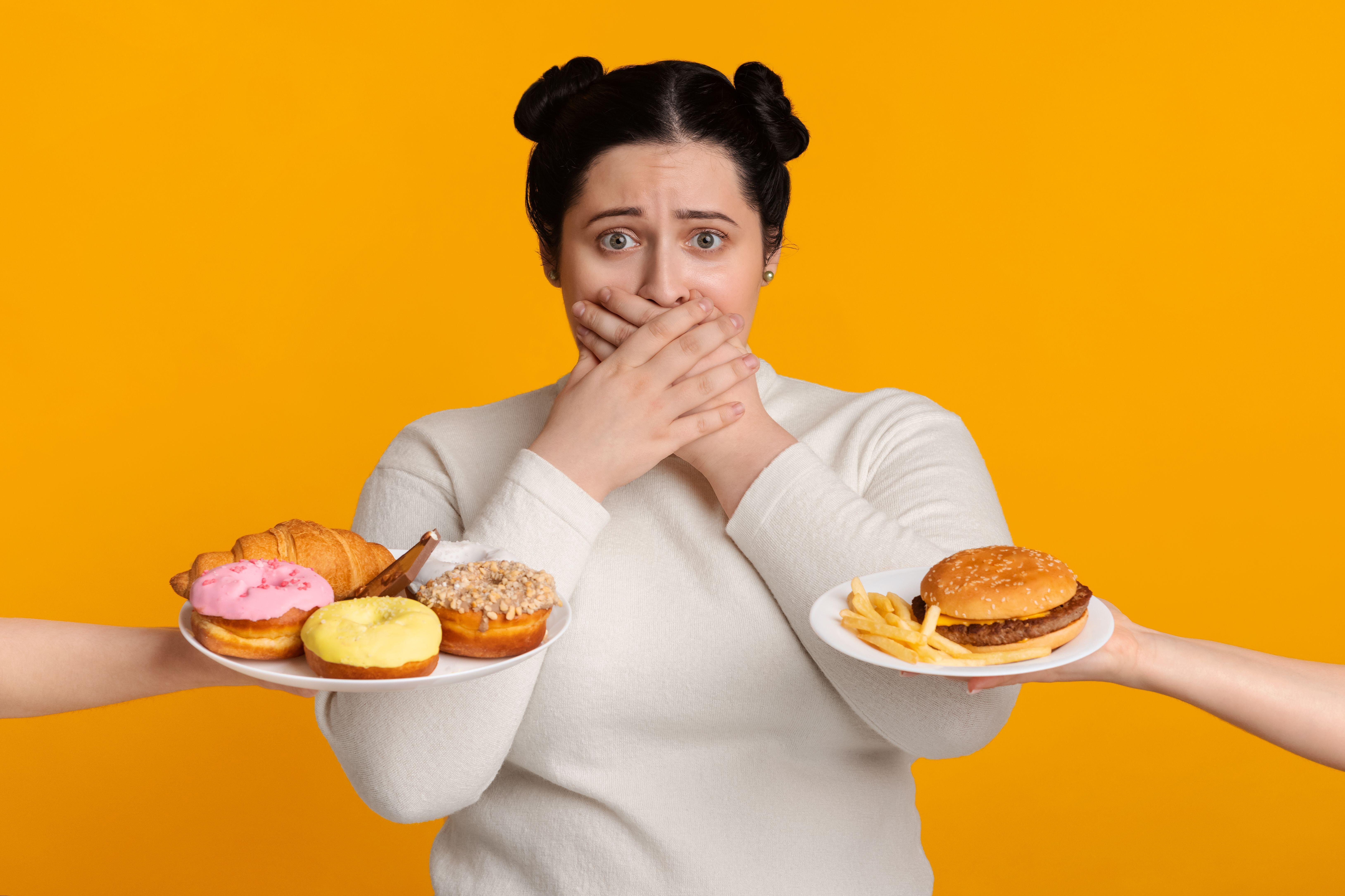 دختری که دهان خود را می پوشاند ، از خوردن غذاهای ناخواسته خودداری می کند